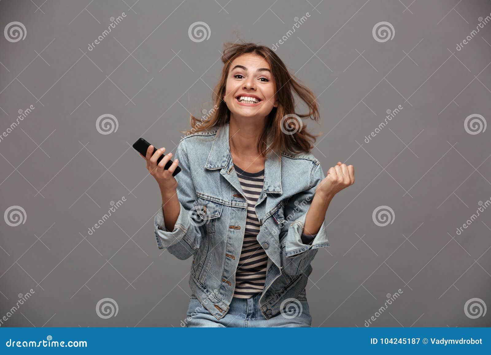 Ευτυχής νέα γυναίκα στο σακάκι τζιν που σφίγγει τις πυγμές της στο νικητή