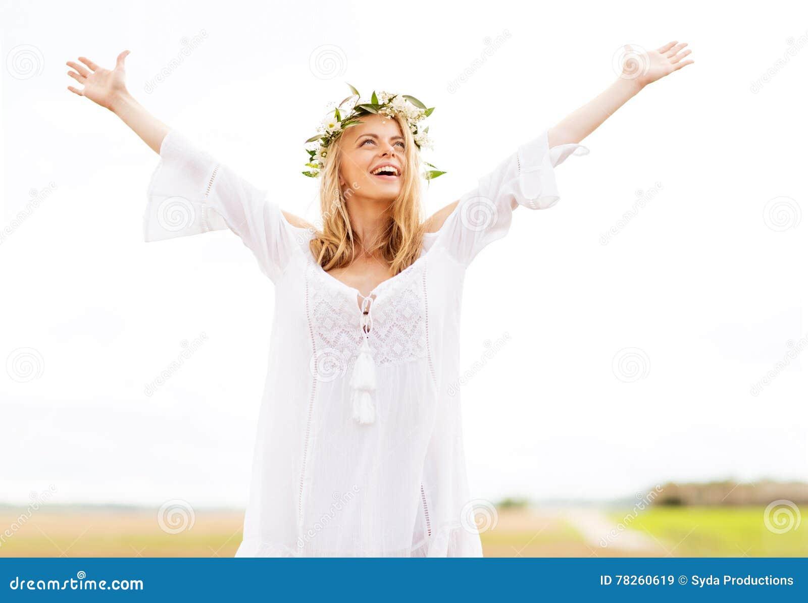 Ευτυχής νέα γυναίκα στο στεφάνι λουλουδιών στον τομέα δημητριακών