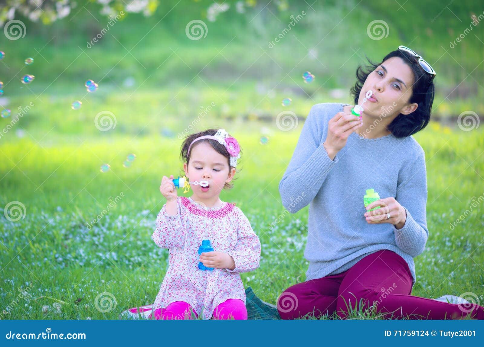 Ευτυχής νέα μητέρα και οι φυσώντας φυσαλίδες σαπουνιών κορών της