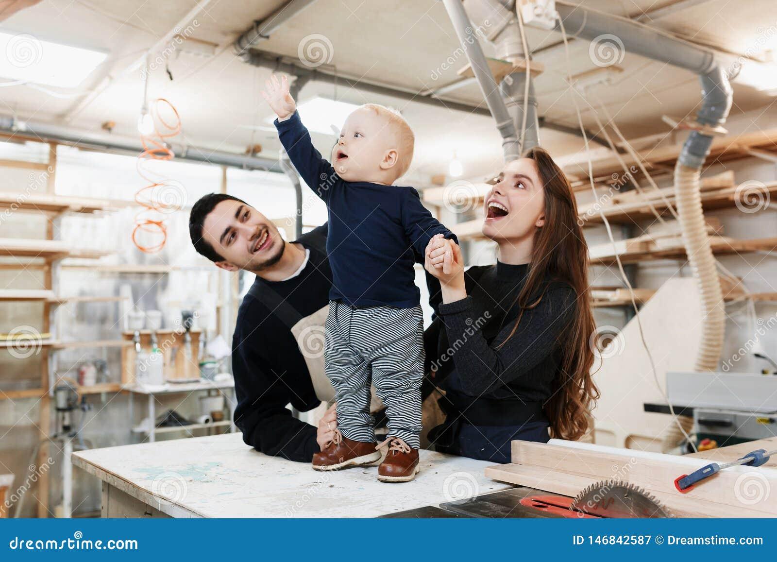 Ευτυχής νέα οικογένεια με το μικρό γιο στο εργαστήριο ξυλουργών