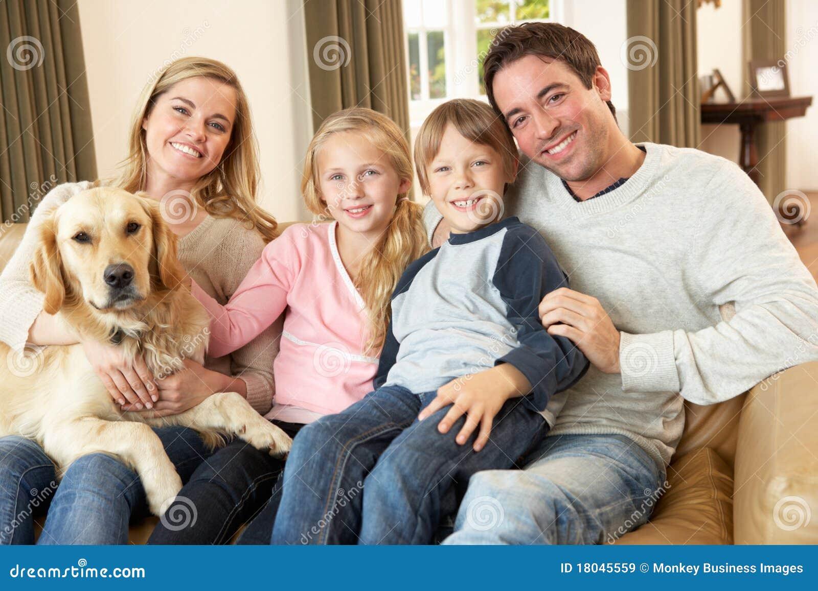 Ευτυχής νέα οικογενειακή συνεδρίαση στον καναπέ που κρατά ένα σκυλί