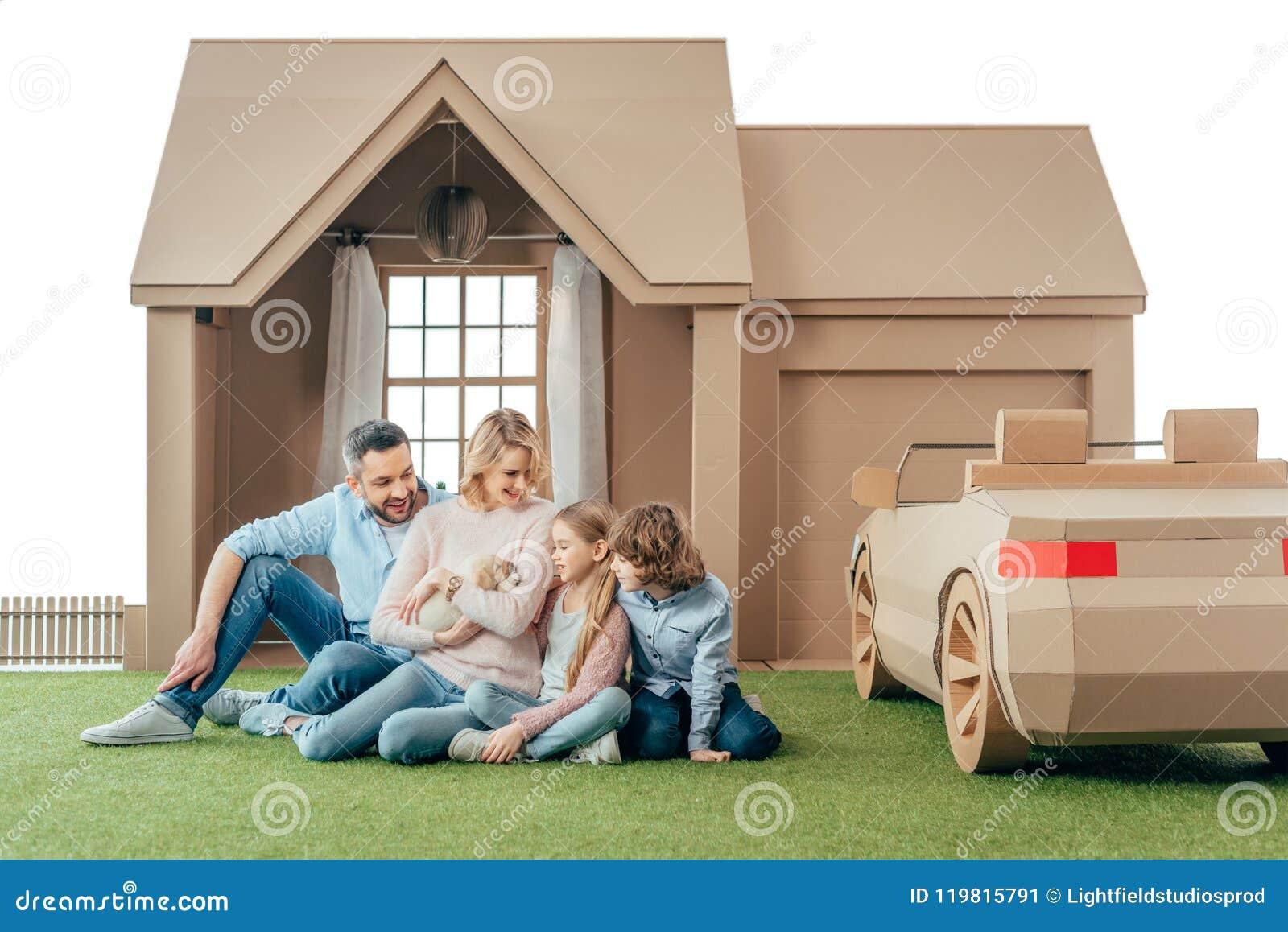 ευτυχής νέα οικογενειακή συνεδρίαση στο ναυπηγείο του σπιτιού χαρτονιού με το κουτάβι τους