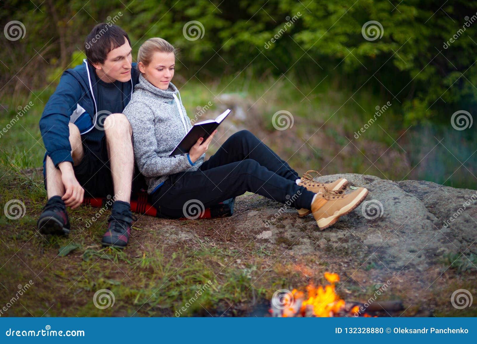 Ευτυχής νέα συνεδρίαση ζευγών κοντά στην πυρά προσκόπων και το βιβλίο ανάγνωσης