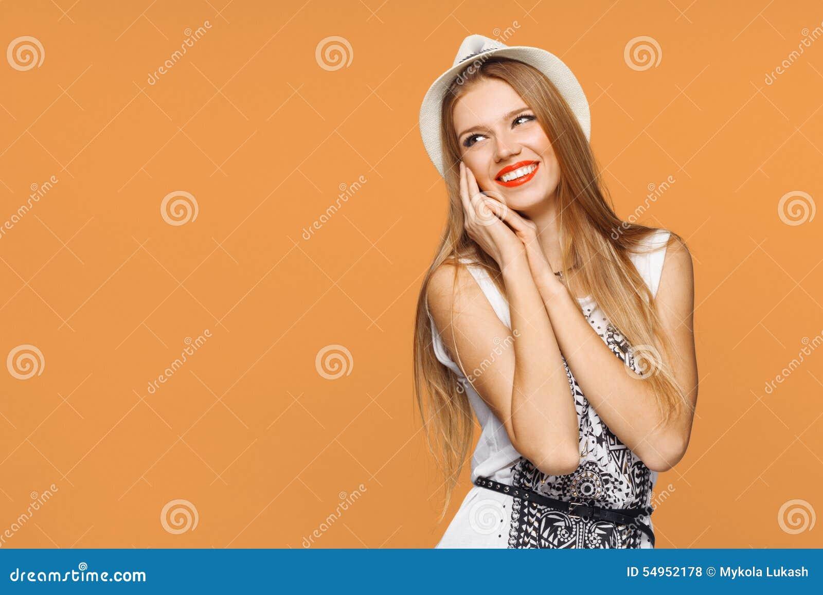 Ευτυχής νέα χαρούμενη γυναίκα που κοιτάζει λοξά στον ενθουσιασμό Απομονωμένος πέρα από το πορτοκαλί υπόβαθρο
