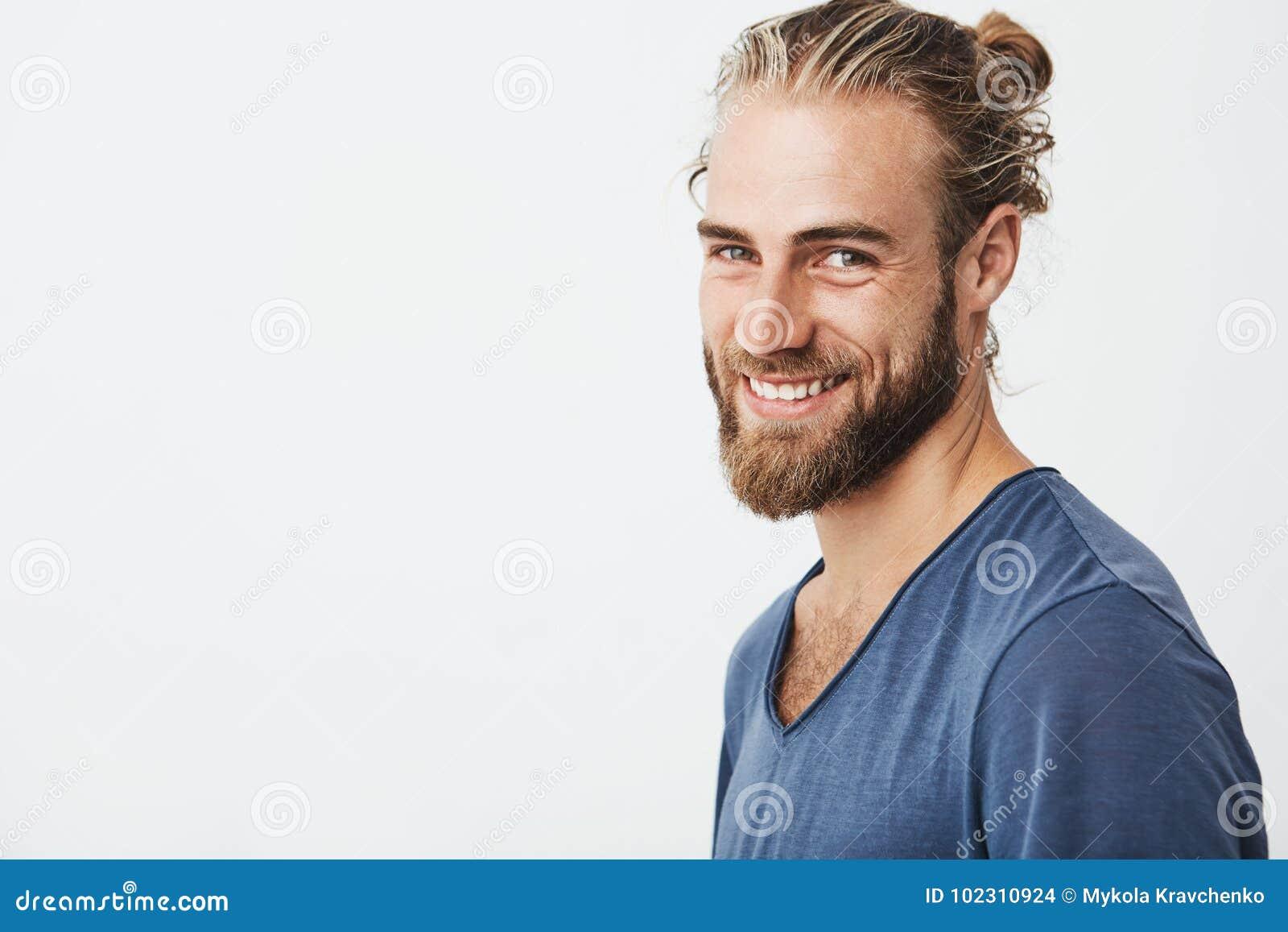 Ευτυχής νέος γενειοφόρος τύπος με το μοντέρνο hairstyle και γενειάδα που εξετάζει τη κάμερα, χαμογελώντας brightfully με τα δόντι