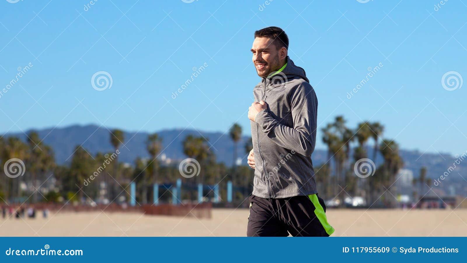 Ευτυχής νεαρός άνδρας που τρέχει πέρα από την παραλία της Βενετίας