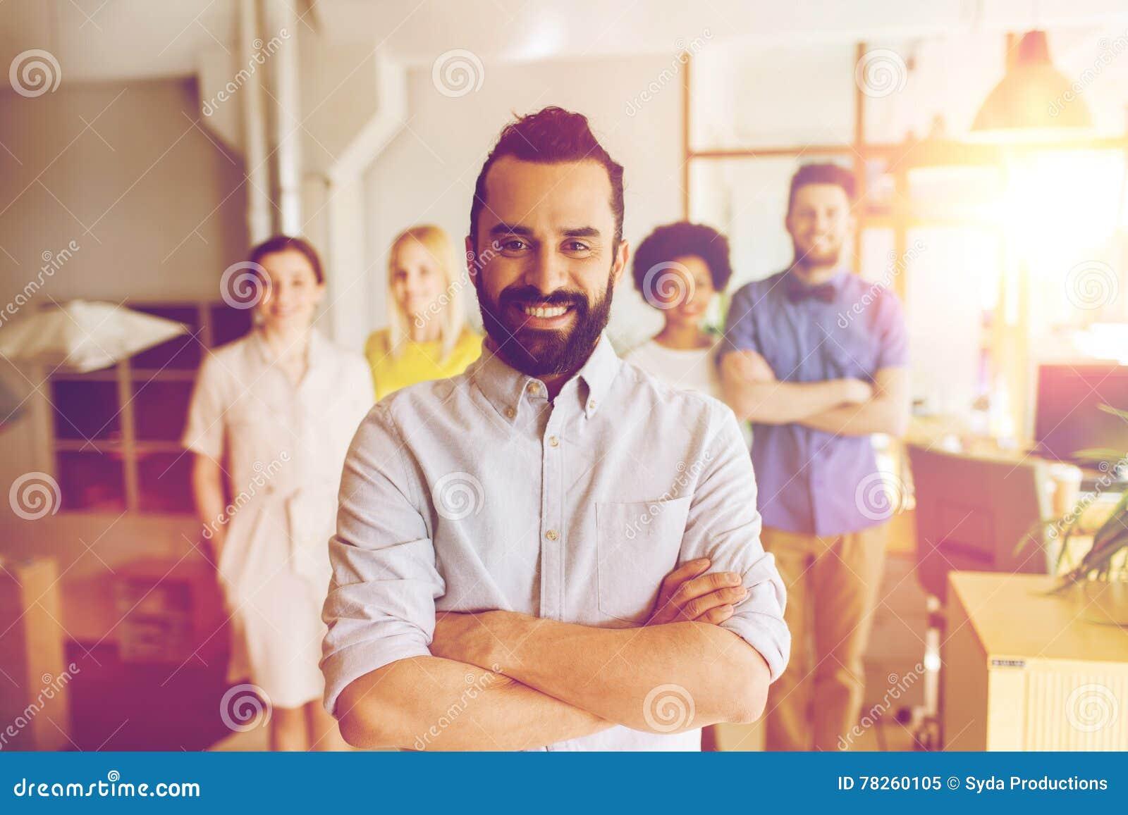 Ευτυχής νεαρός άνδρας πέρα από τη δημιουργική ομάδα στην αρχή