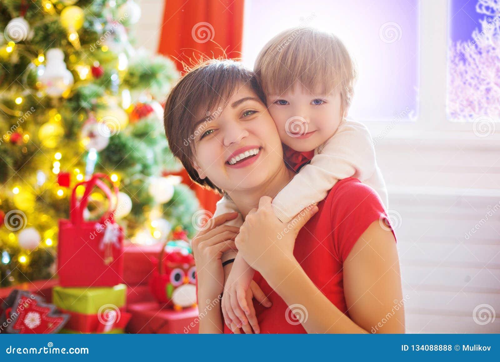 Ευτυχής οικογένεια και Χαρούμενα Χριστούγεννα Γιος μητέρων και μωρών στο πρωί Χριστουγέννων