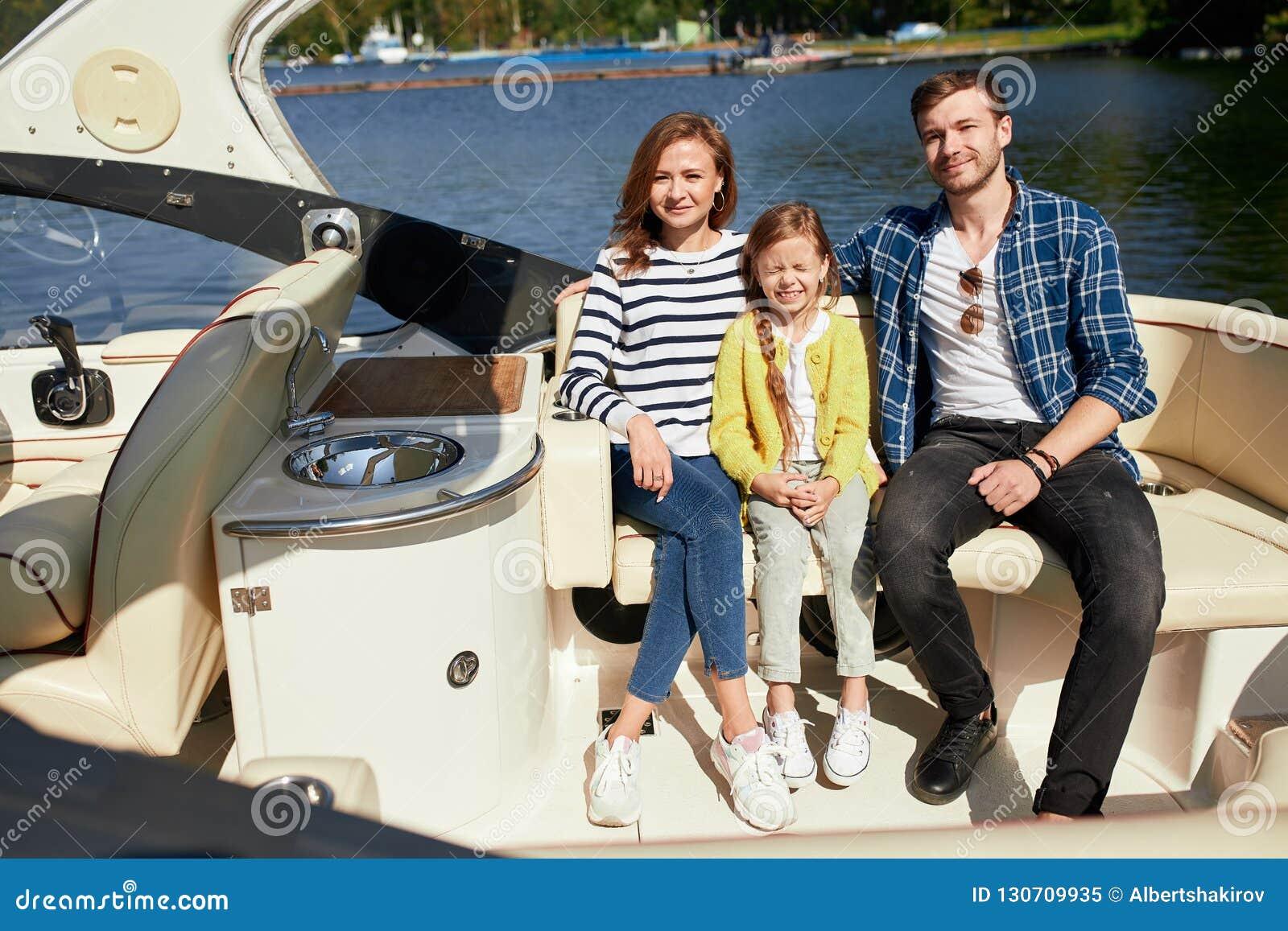 Ευτυχής οικογένεια με την κόρη στην πλέοντας βάρκα στην ηλιόλουστη ημέρα φθινοπώρου