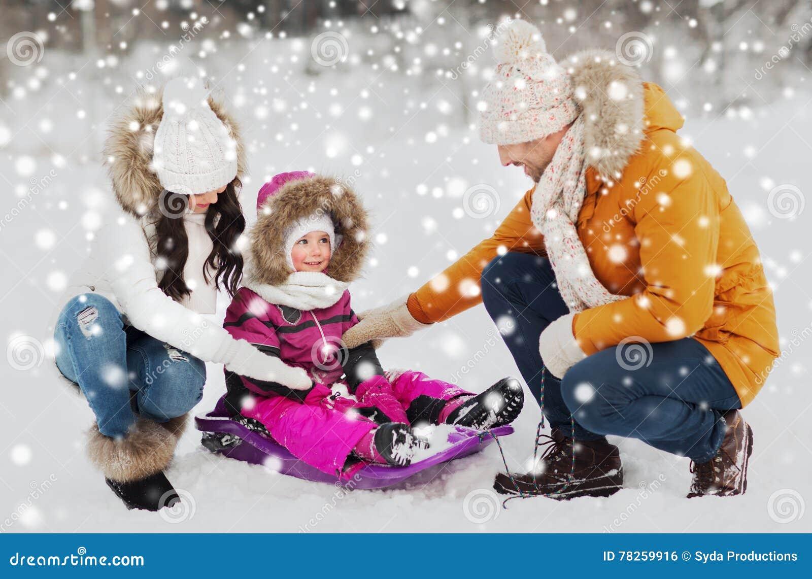 Ευτυχής οικογένεια με το έλκηθρο που περπατά στο χειμερινό δάσος
