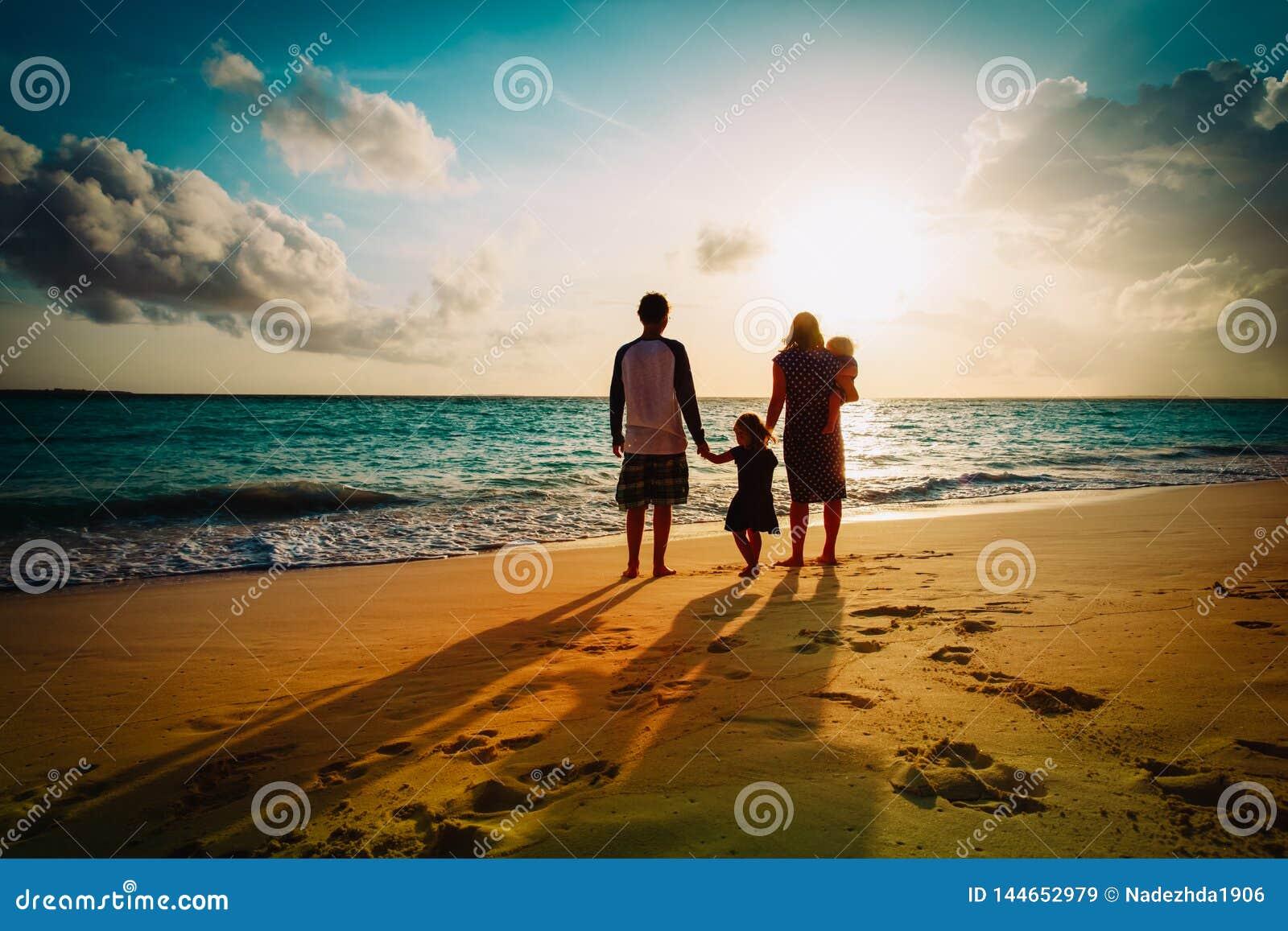 Ευτυχής οικογένεια με το παιχνίδι παιδιών στην παραλία ηλιοβασιλέματος