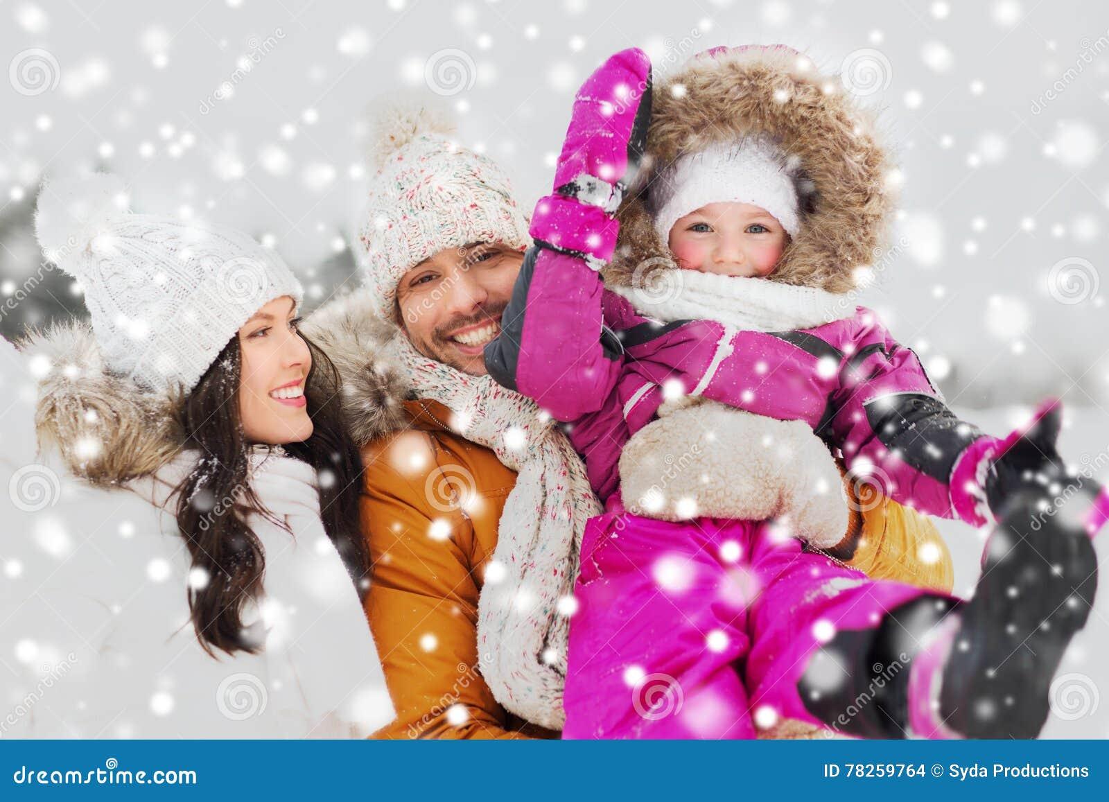 Ευτυχής οικογένεια με το παιδί στα χειμερινά ενδύματα υπαίθρια
