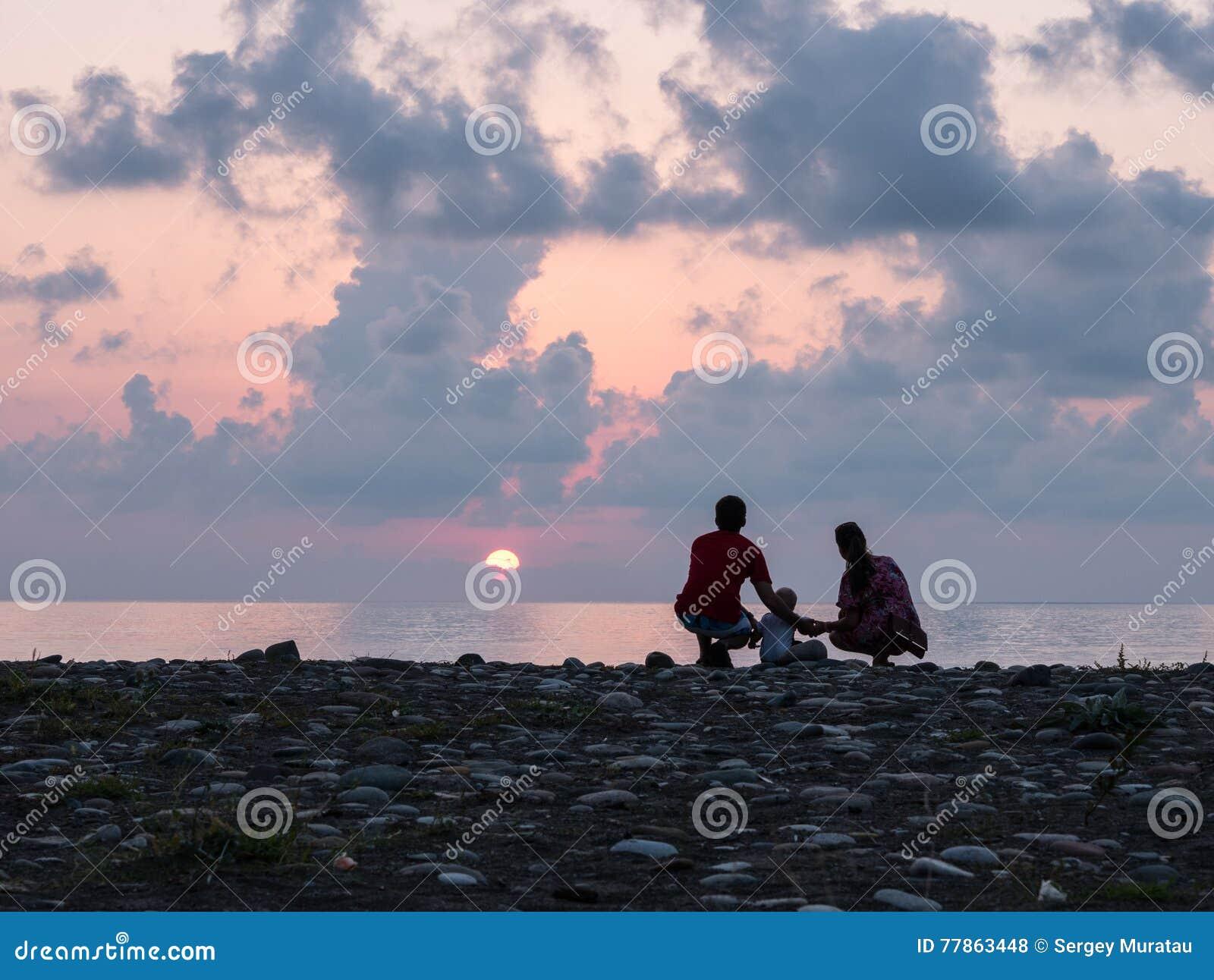 Ευτυχής οικογένεια - ο πατέρας, μητέρα, γιος μωρών βλέπει την κυματωγή θάλασσας ηλιοβασιλέματος στη μαύρη παραλία άμμου Ενεργοί γ