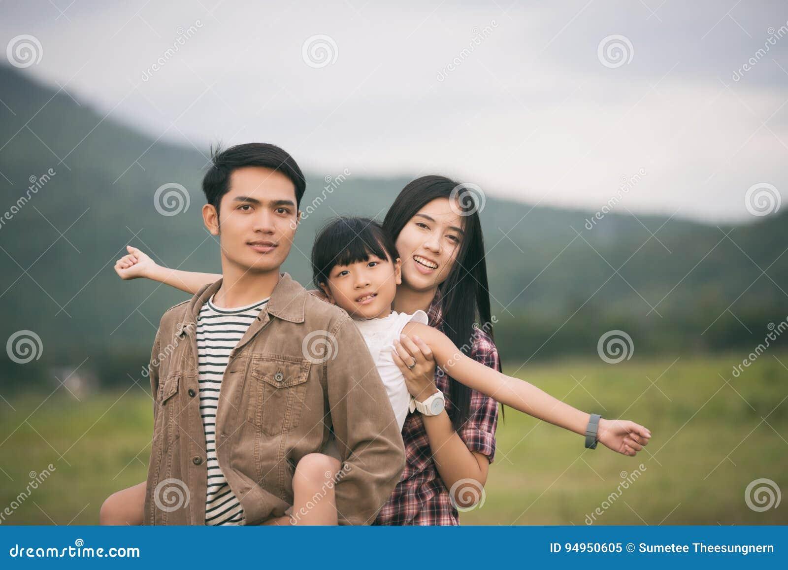 Ευτυχής οικογένεια που έχει τη διασκέδαση και που απολαμβάνει το ταξίδι στο πάρκο