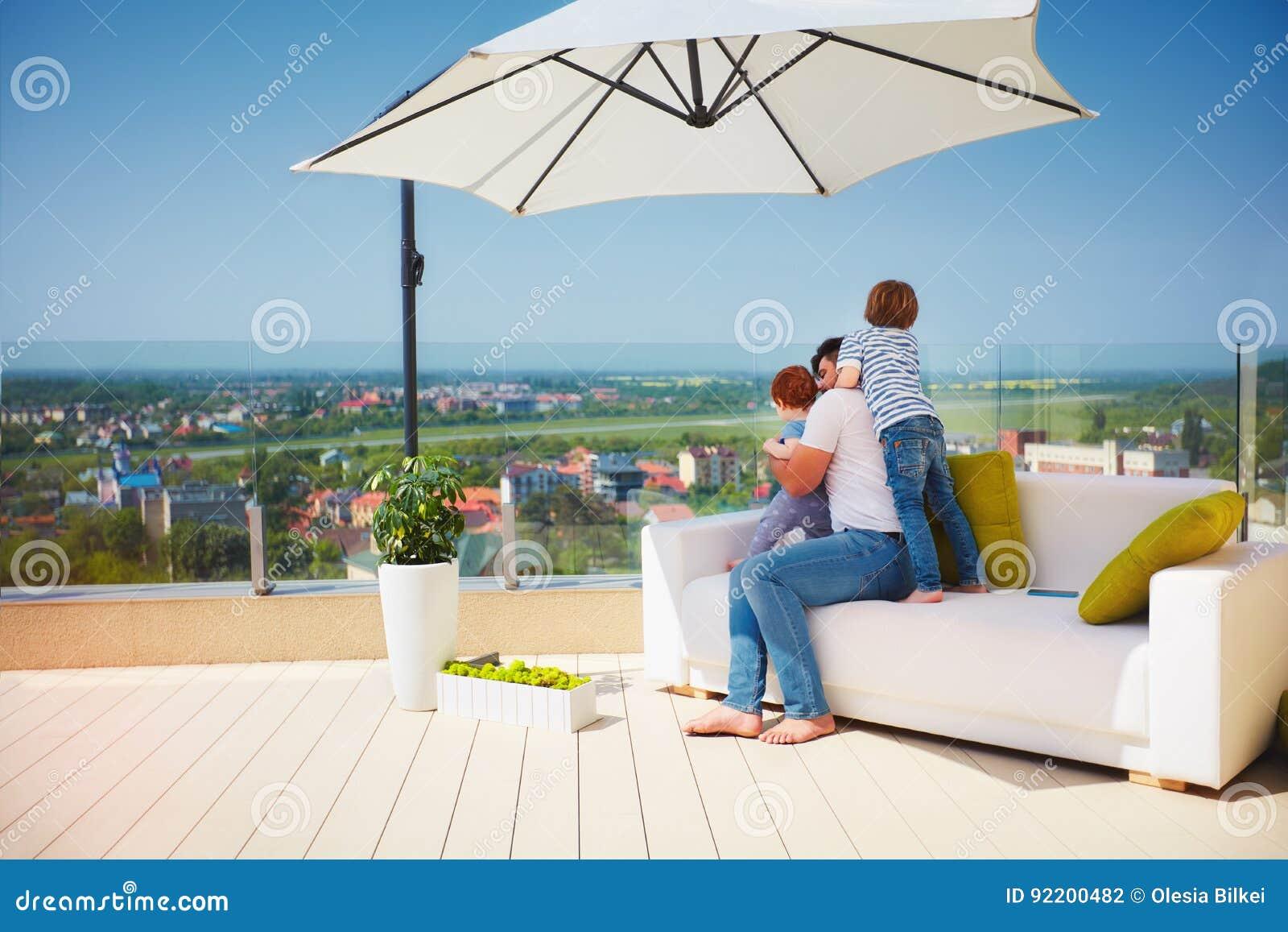 Ευτυχής οικογένεια που απολαμβάνει τη θέα, που χαλαρώνει στον καναπέ στο τοπ πεζούλι στεγών στη θερμή ηλιόλουστη ημέρα