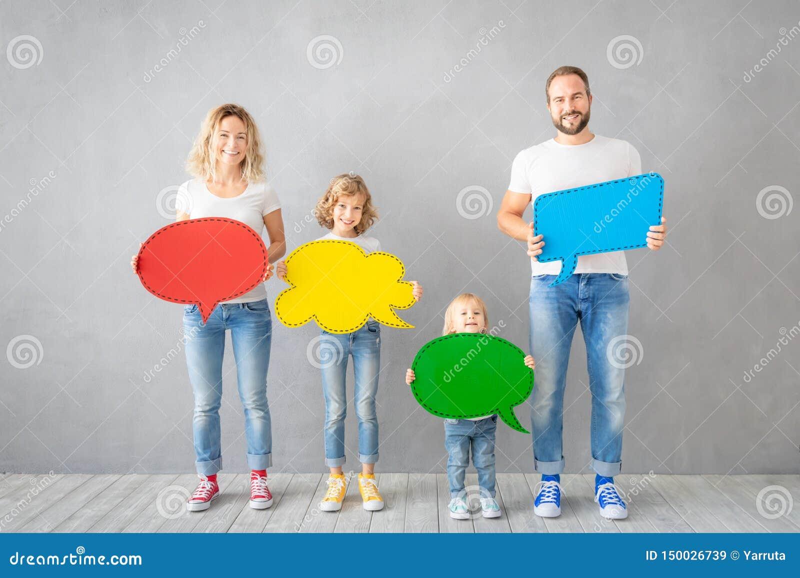 Ευτυχής οικογένεια που κρατά το ζωηρόχρωμο κενό λεκτικών φυσαλίδων εγγράφου