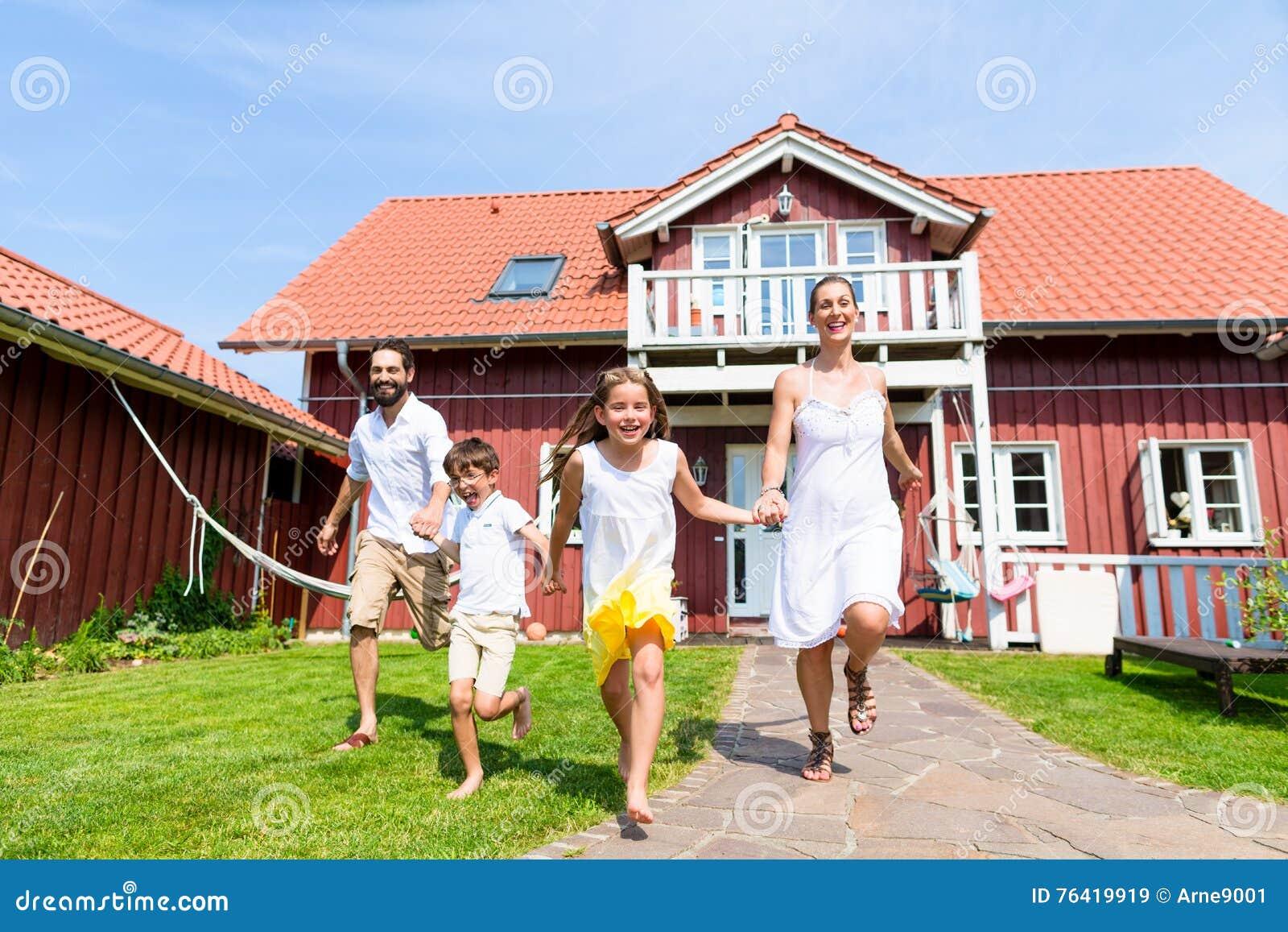 Ευτυχής οικογένεια που τρέχει στο λιβάδι μπροστά από το σπίτι