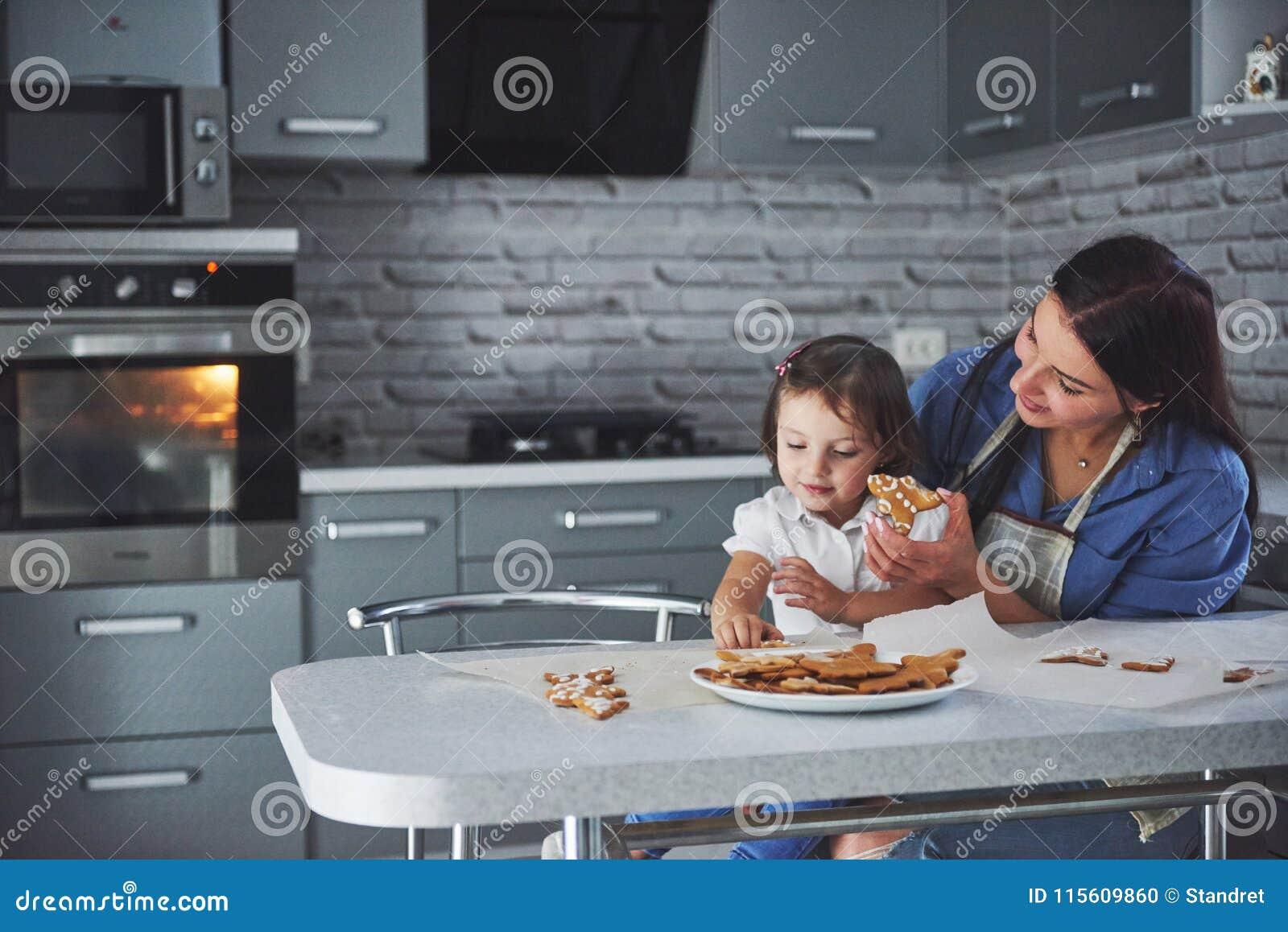 Ευτυχής οικογένεια στην κουζίνα Έννοια τροφίμων διακοπών Η μητέρα και η κόρη διακοσμούν τα μπισκότα Ευτυχής οικογένεια στην παραγ
