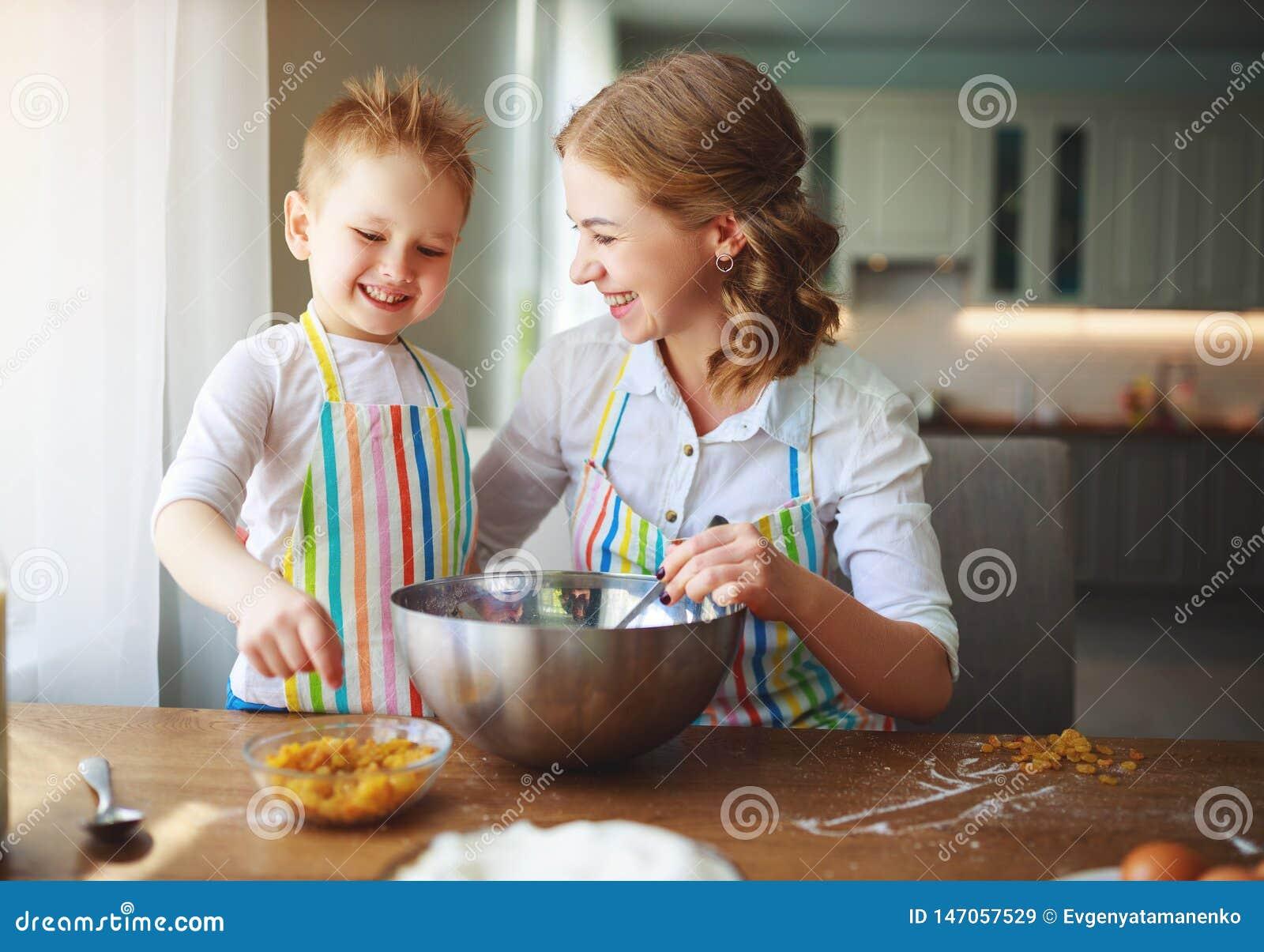Ευτυχής οικογένεια στην κουζίνα η μητέρα και το παιδί που προετοιμάζουν τη ζύμη, ψήνουν τα μπισκότα