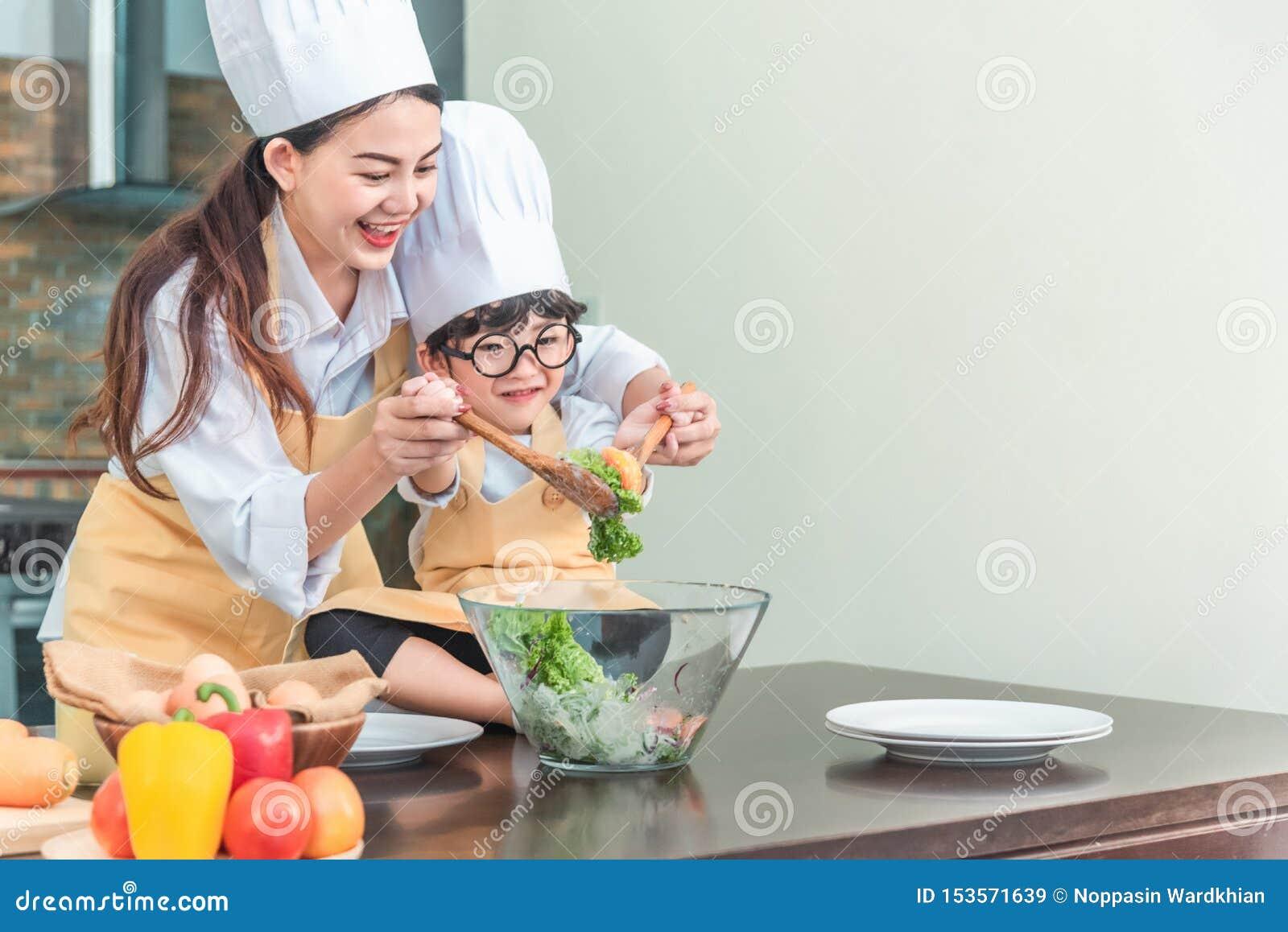 Ευτυχής οικογένεια στην κουζίνα κόρη μητέρων και παιδιών που προετοιμάζει τη ζύμη, σαλάτα