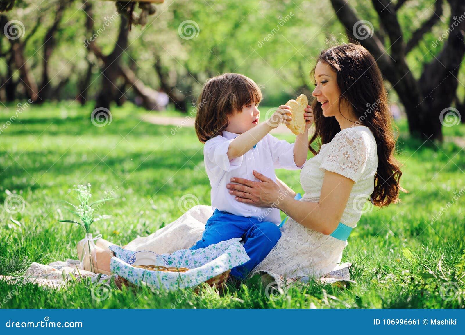 Ευτυχής οικογένεια στο πικ-νίκ για την ημέρα μητέρων Γιος Mom και μικρών παιδιών που τρώει τα γλυκά υπαίθρια την άνοιξη