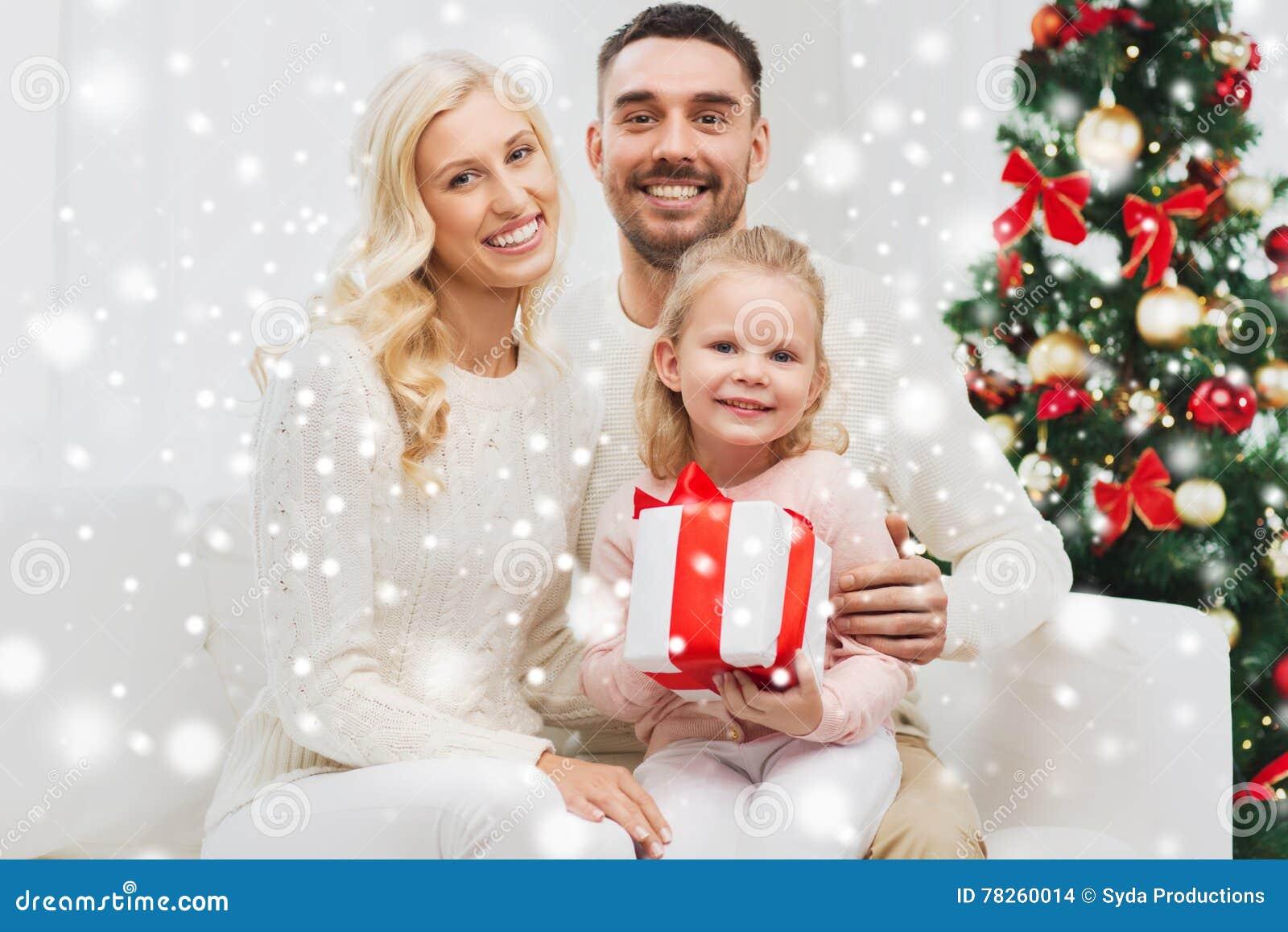 Ευτυχής οικογένεια στο σπίτι με το κιβώτιο δώρων Χριστουγέννων