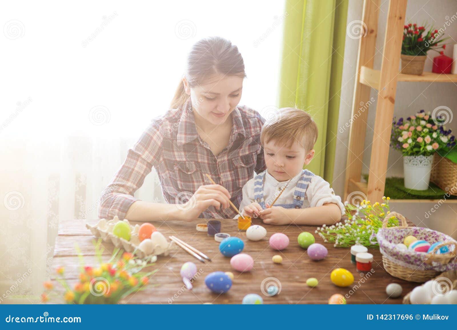 Ευτυχής οικογένεια Mom και αυγά Πάσχας χρωμάτων γιων παιδιών με τα χρώματα Προετοιμασία για τις διακοπές