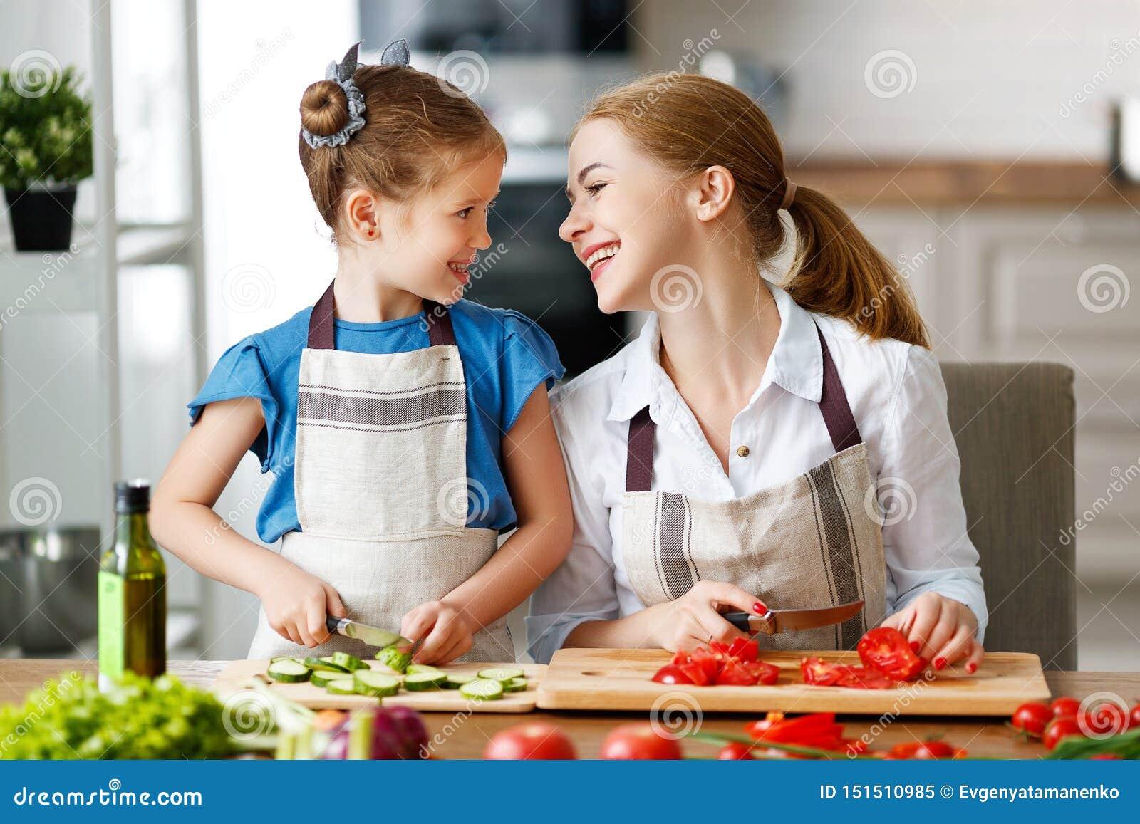 Ευτυχής οικογενειακή μητέρα με το κορίτσι παιδιών που προετοιμάζει τη φυτική σαλάτα
