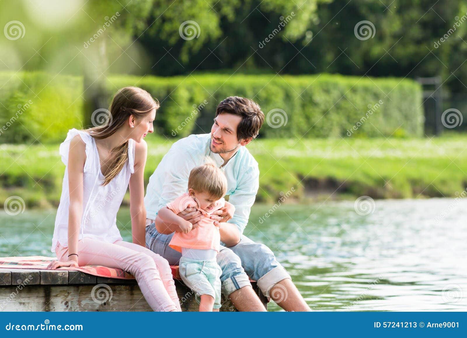 Ευτυχής οικογενειακή συνεδρίαση στο λιμενοβραχίονα στη λίμνη ή τη λίμνη