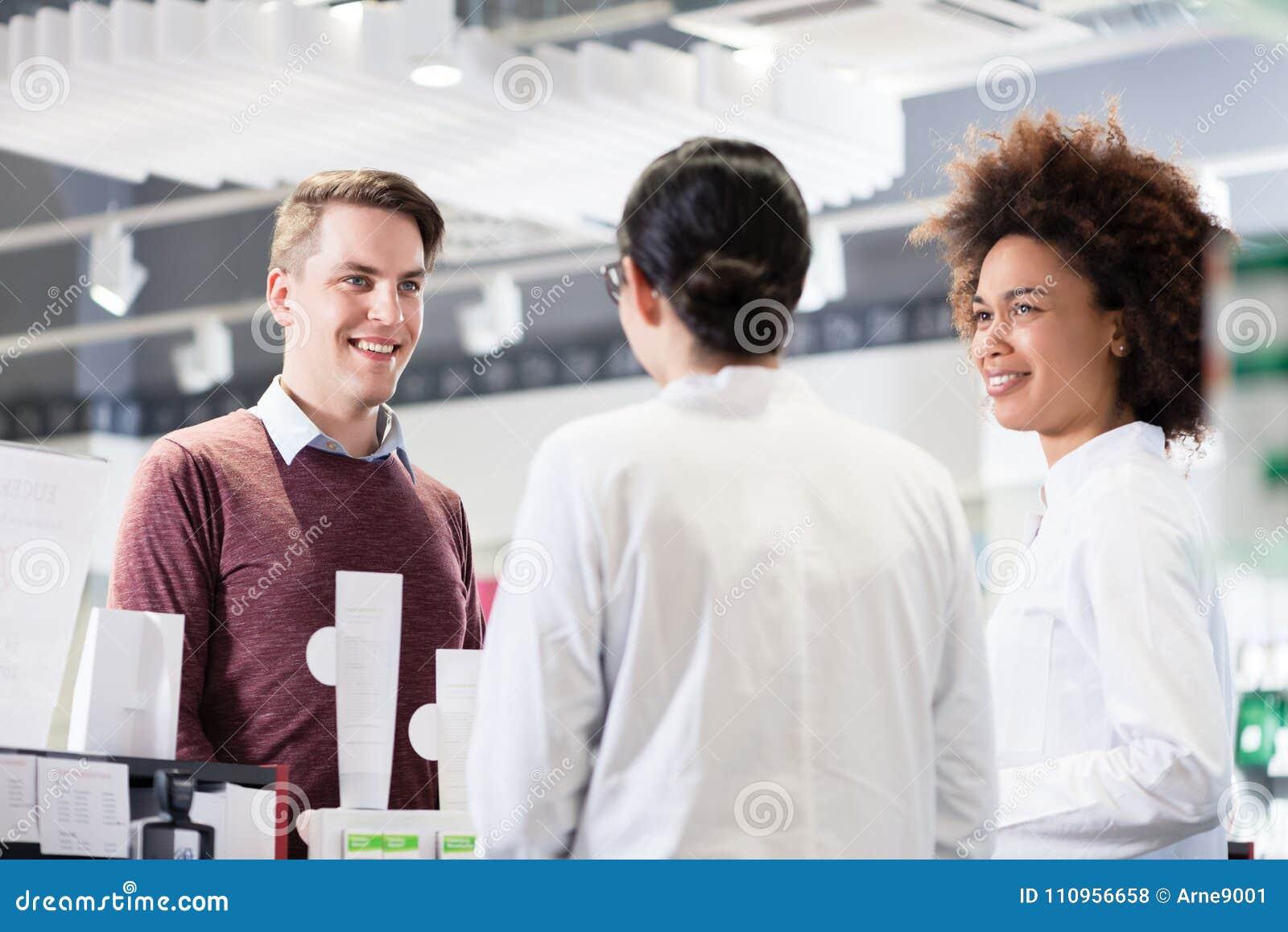 Ευτυχής πελάτης που μιλά με δύο χρήσιμους φαρμακοποιούς σε ένα σύγχρονο φαρμακείο