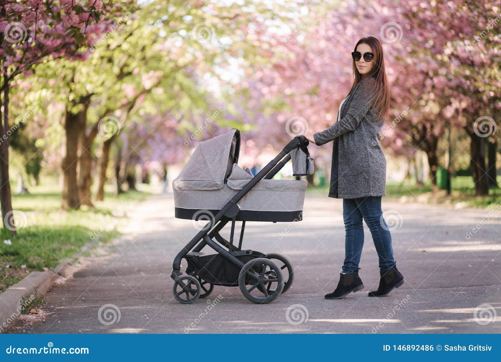 Ευτυχής περίπατος mom με την λίγο κοριτσάκι στον περιπατητή Υπόβαθρο του ρόδινου δέντρου sakura