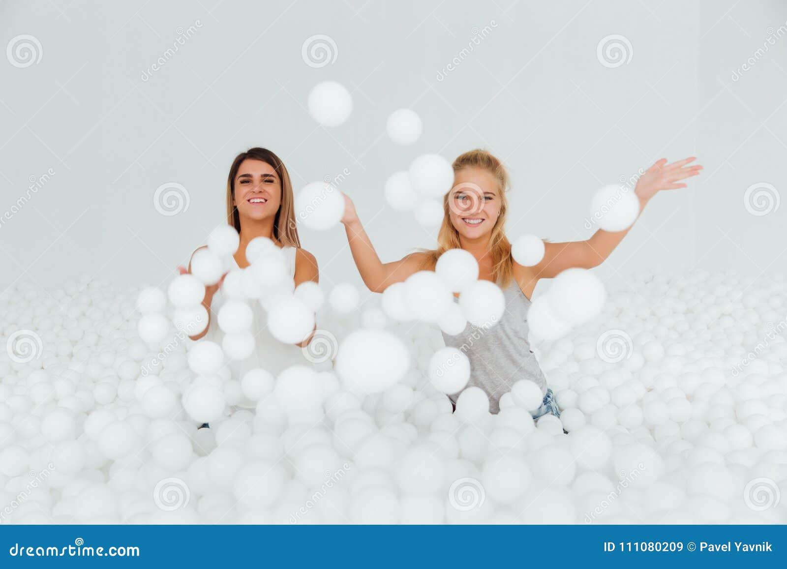 Ευτυχής στάση φίλων πορτρέτου που περιβάλλεται από τις άσπρες πλαστικές σφαίρες στην ξηρά λίμνη