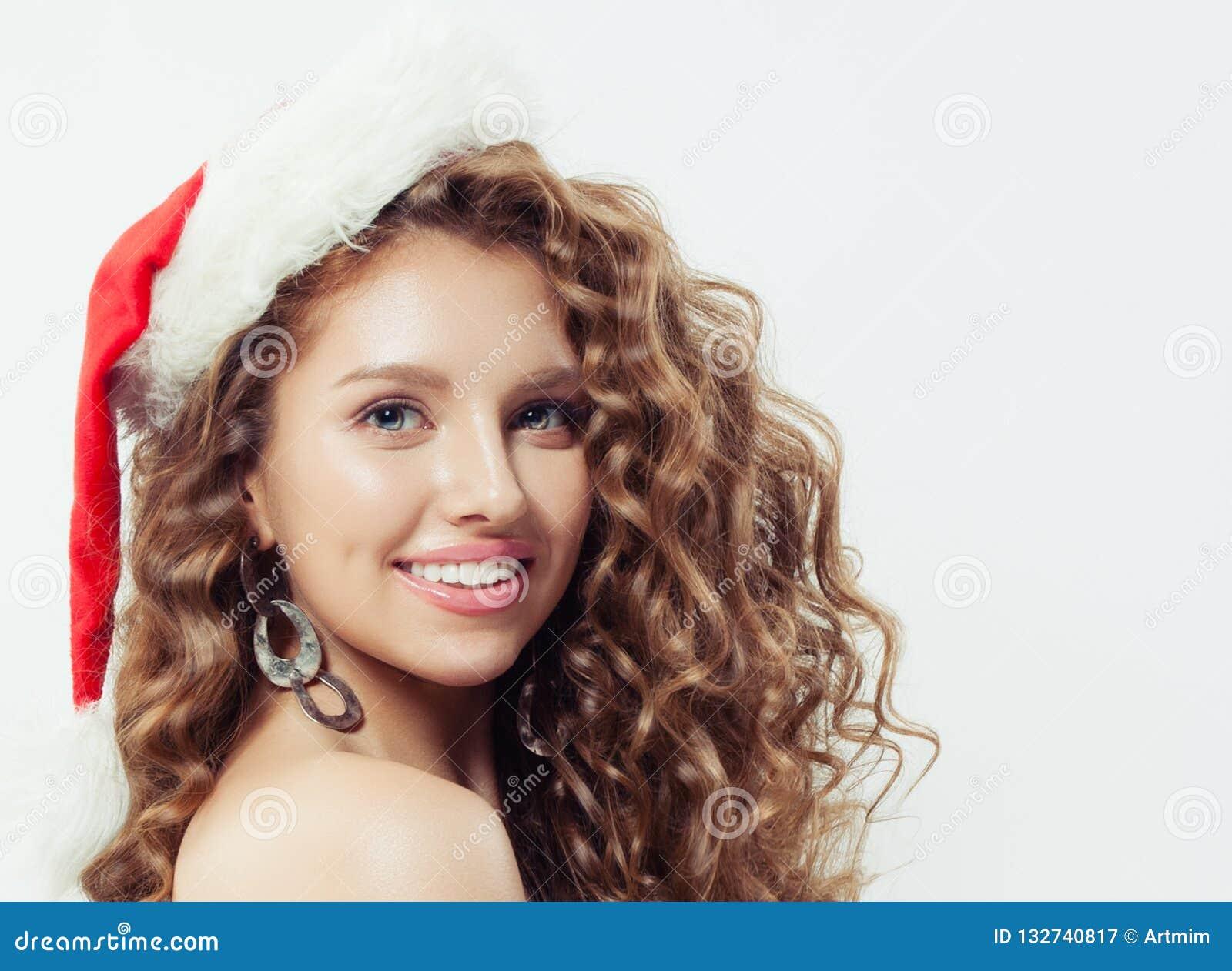 Ευτυχής συγκινημένη νέα γυναίκα στο χαμόγελο καπέλων Santa