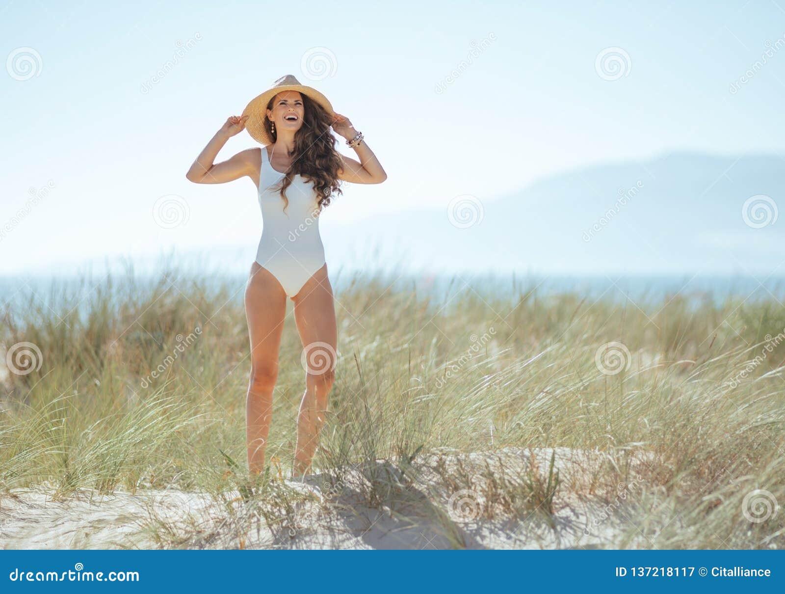 Ευτυχής σύγχρονη γυναίκα στην άσπρη beachwear στάση στην ακτή