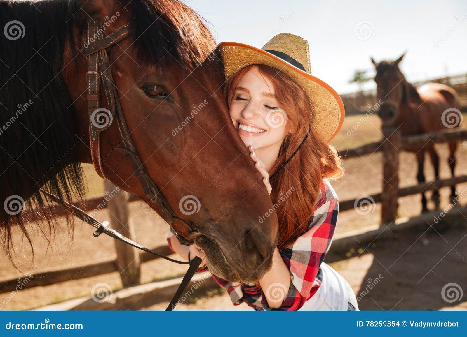 Ευτυχής τρυφερή νέα γυναίκα cowgirl που αγκαλιάζει το άλογό της