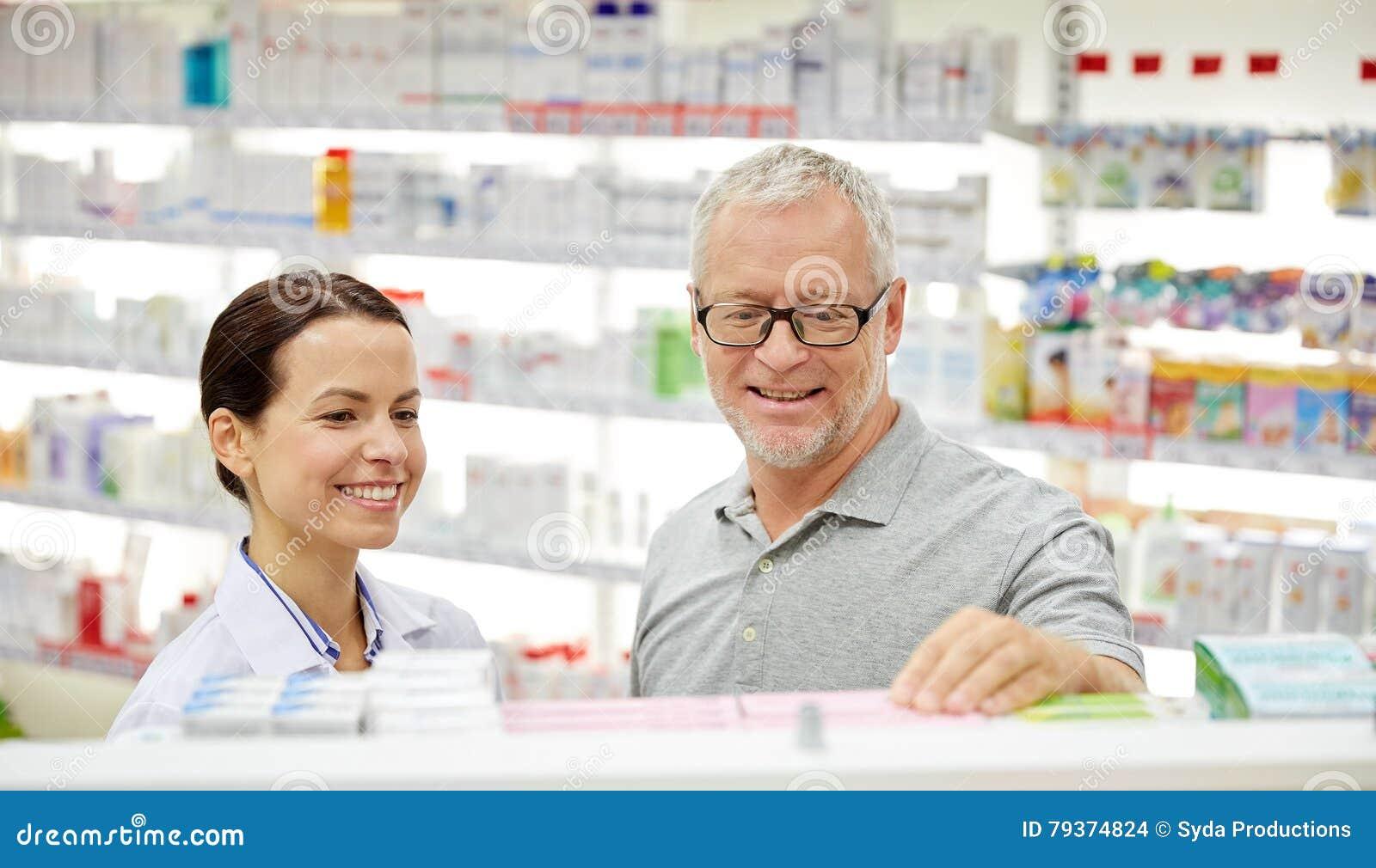 Ευτυχής φαρμακοποιός που μιλά στο ανώτερο άτομο στο φαρμακείο
