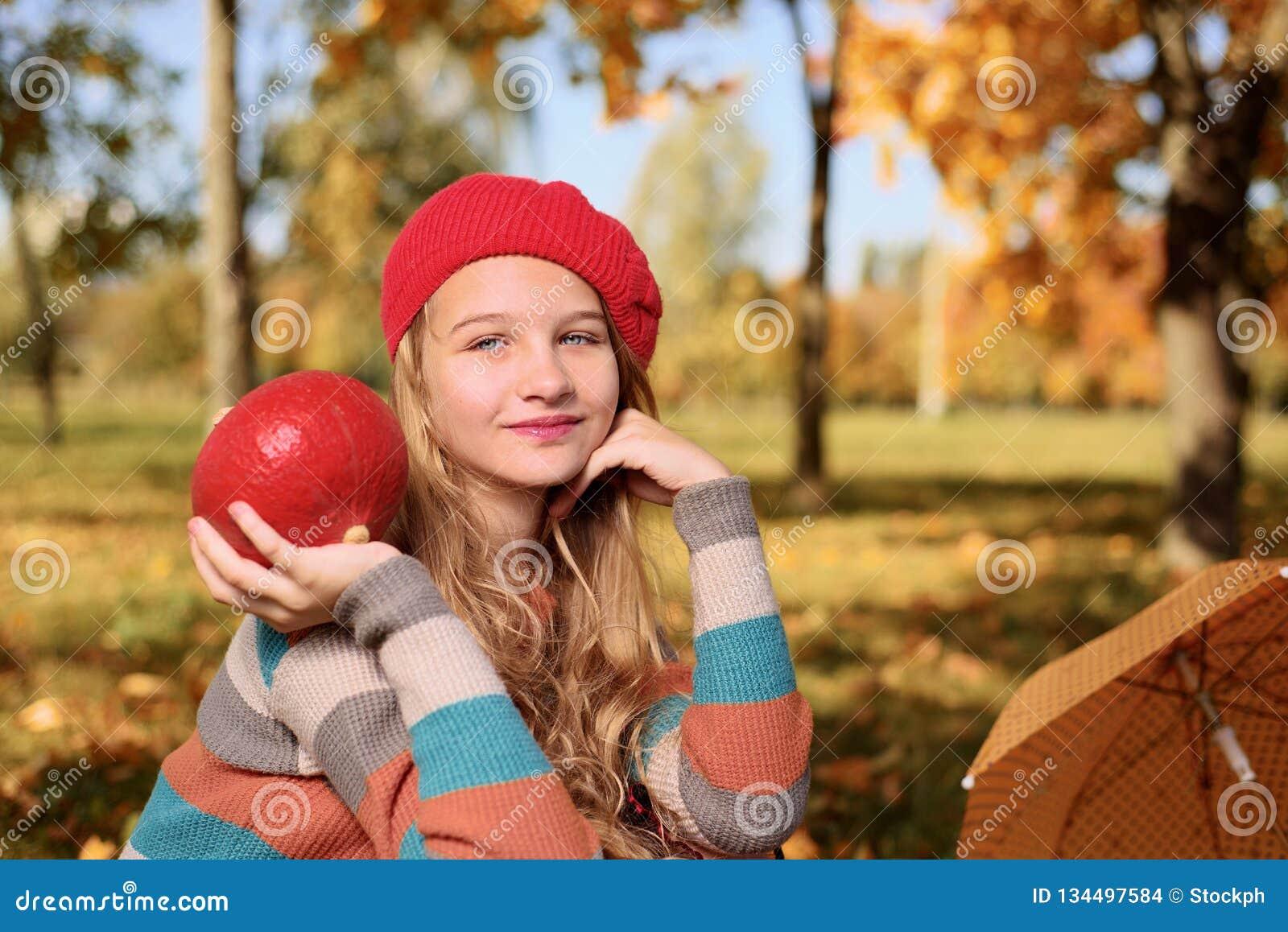 ευτυχής χαμογελώντας έφ&e Πορτρέτο φθινοπώρου του όμορφου νέου κοριτσιού στο κόκκινο καπέλο
