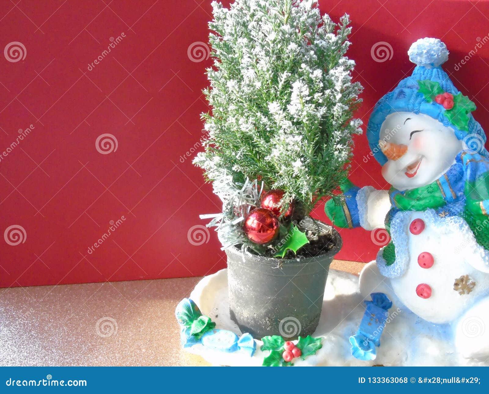 Ευτυχής χαρούμενος χιονάνθρωπος Χριστουγέννων που κάνει πατινάζ γύρω από ένα χριστουγεννιάτικο δέντρο