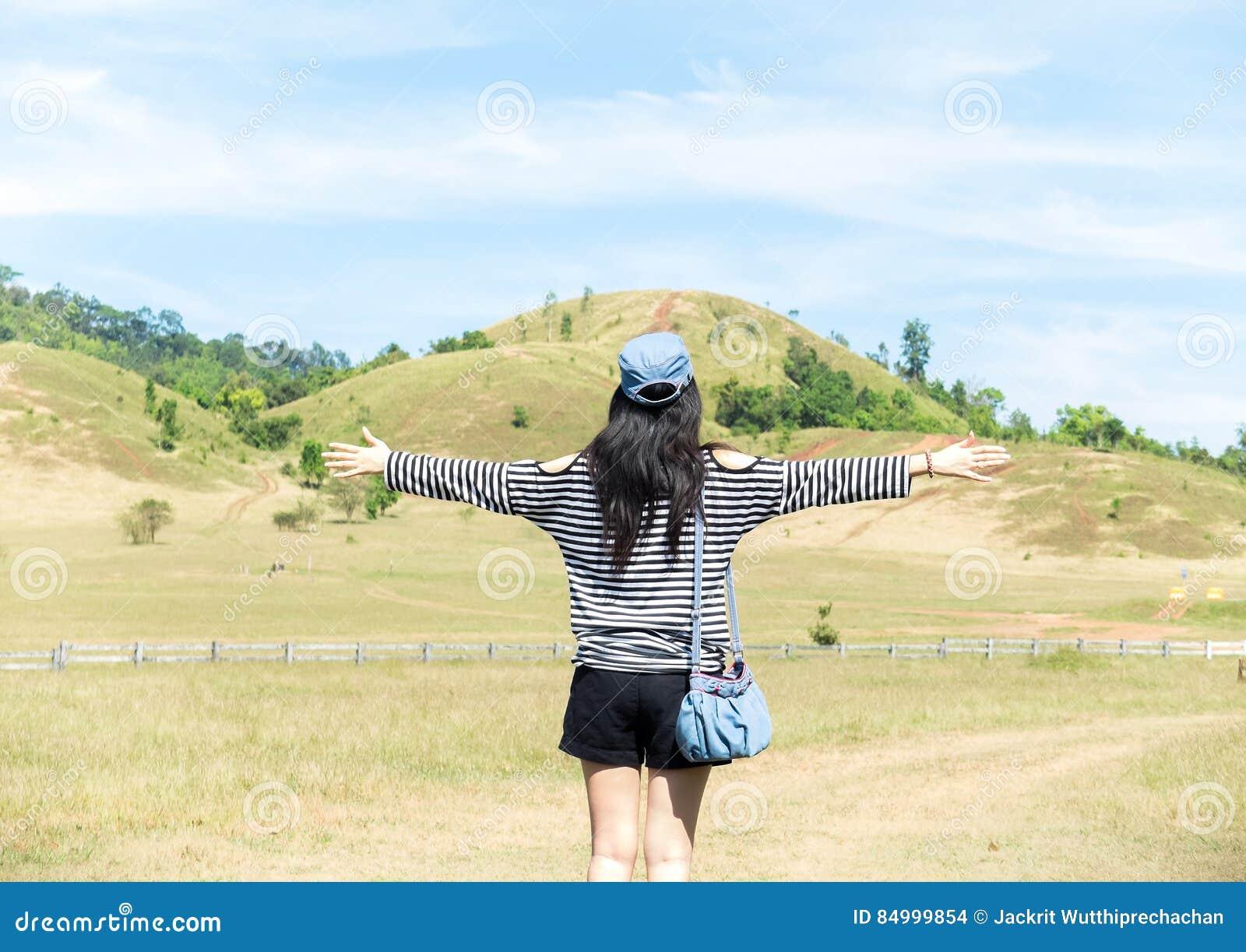 ea1c36fa2f Ευτυχής όμορφη ασιατική γυναίκα με το καπέλο και τσάντα έτοιμη να αρχίσει  τις διακοπές με τη φύση βουνών τοπίου στο υπόβαθρο Πηγαίνετε έννοια  ταξιδιού ...