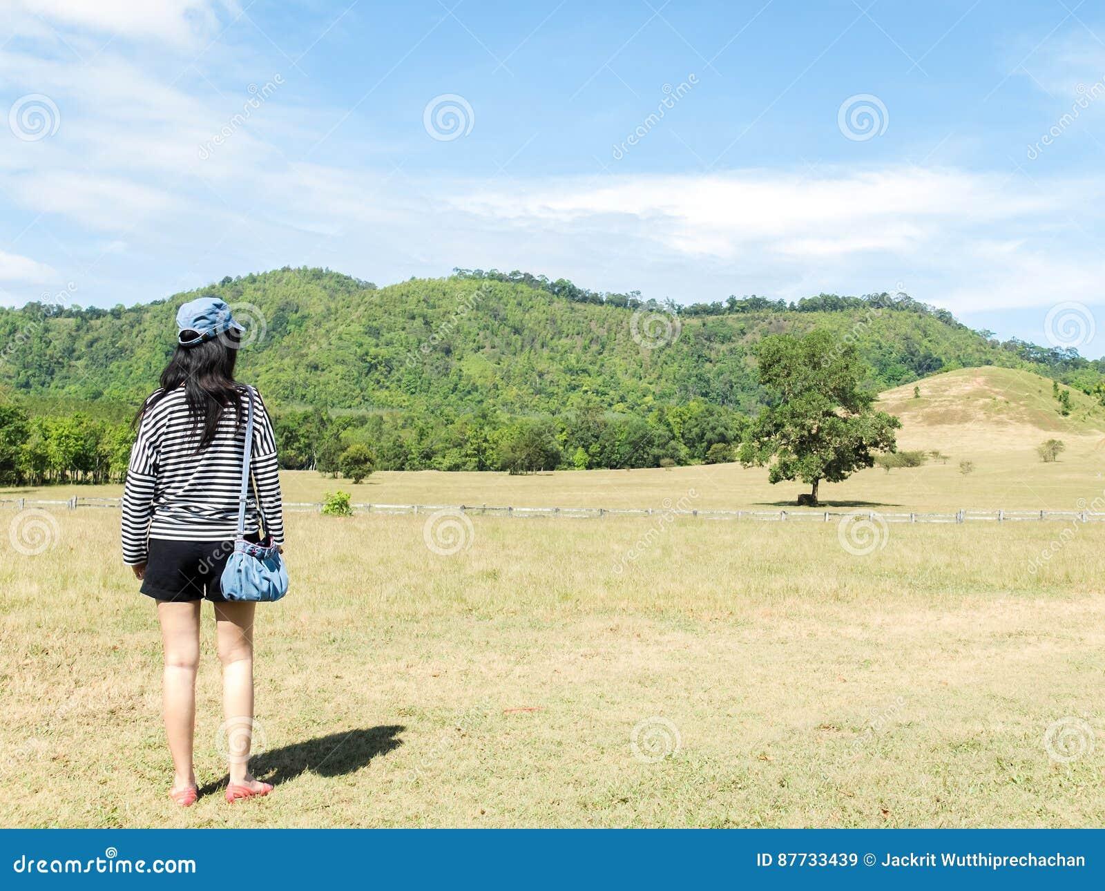 b134b91380 Ευτυχής όμορφη ασιατική γυναίκα με το καπέλο και τσάντα έτοιμη να αρχίσει  τις διακοπές στη γωνία με τη φύση βουνών τοπίου στο υπόβαθρο Πηγαίνετε  έννοια ...