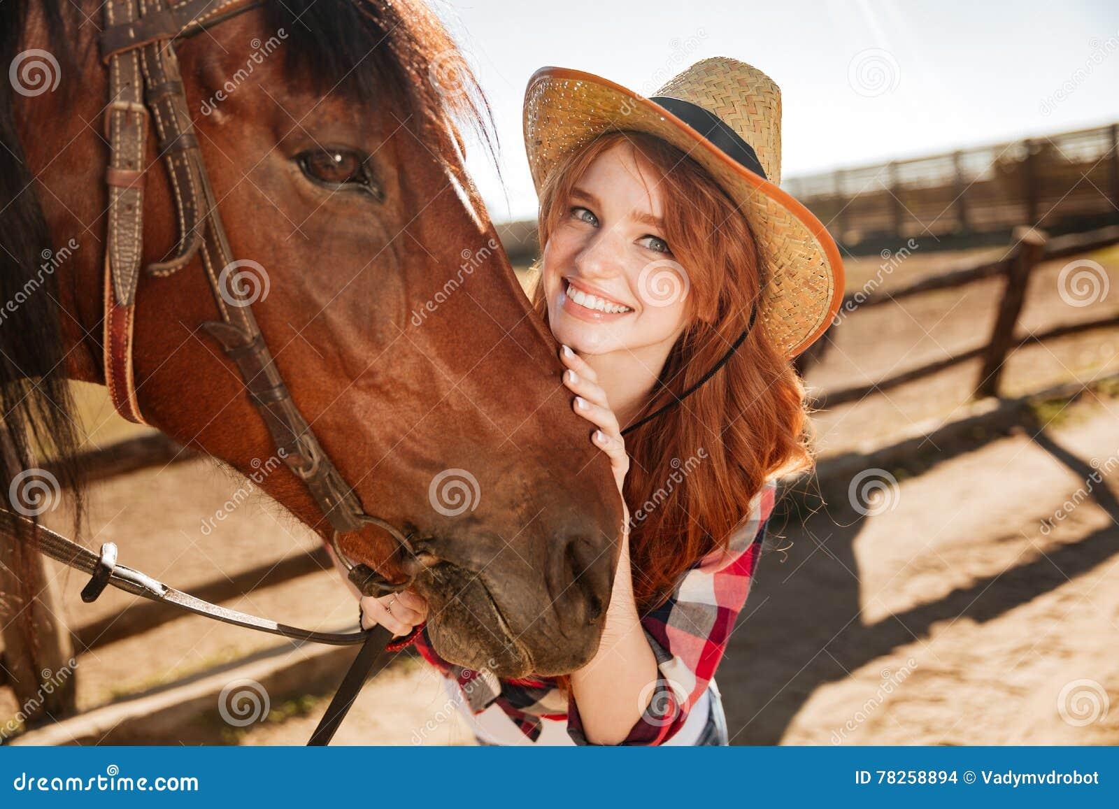 Ευτυχής όμορφη νέα γυναίκα cowgirl με το άλογό της στο αγρόκτημα