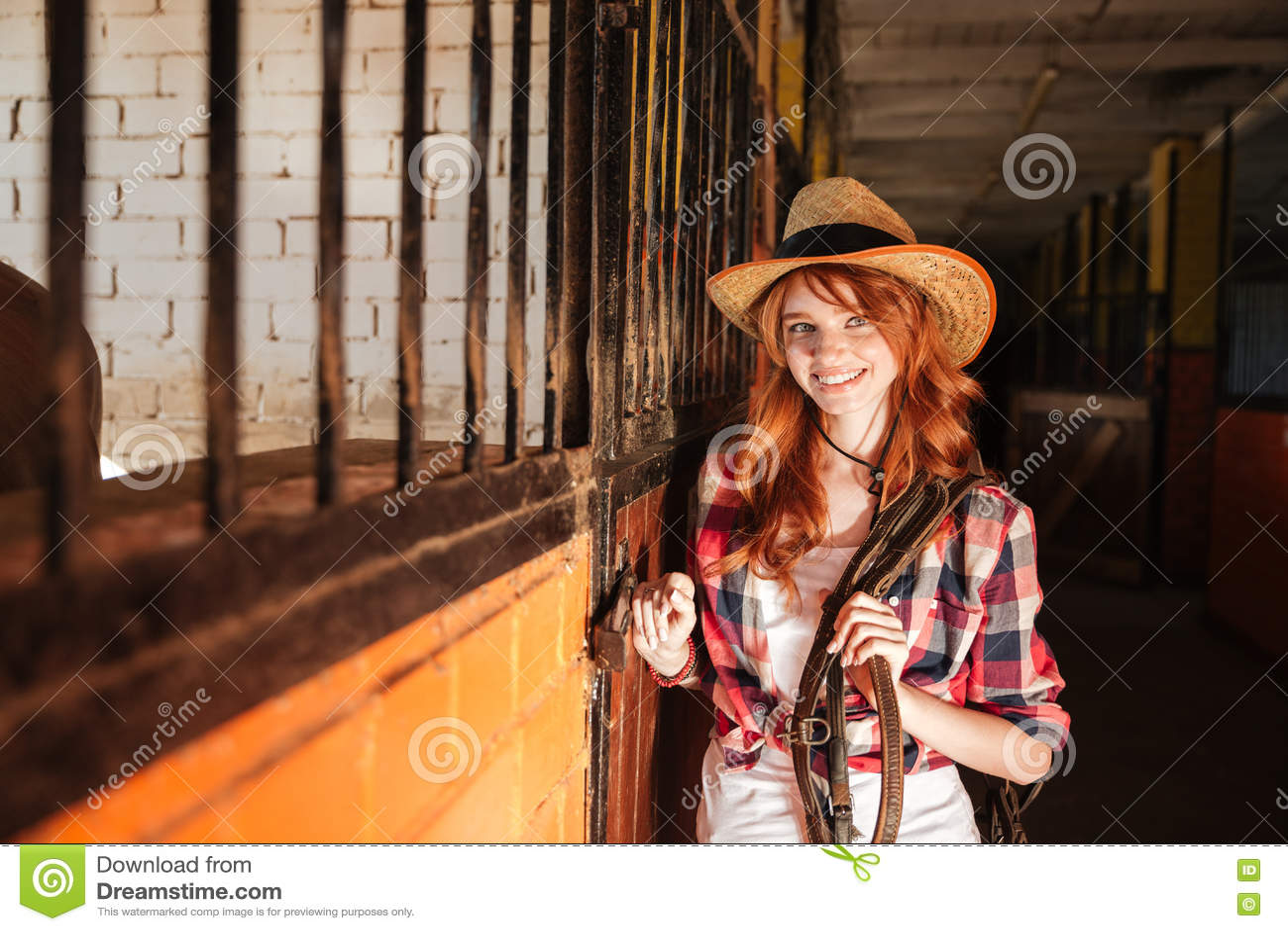 Ευτυχής όμορφη νέα γυναίκα cowgirl που στέκεται στο σταύλο