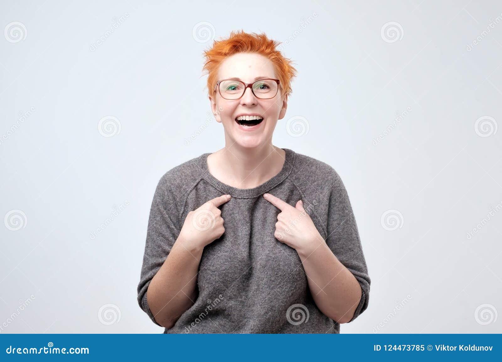 Ευτυχής ώριμη γυναίκα με την κόκκινη τρίχα που δείχνει τα δάχτυλα σε την Με επιλέξτε παρακαλώ έννοια