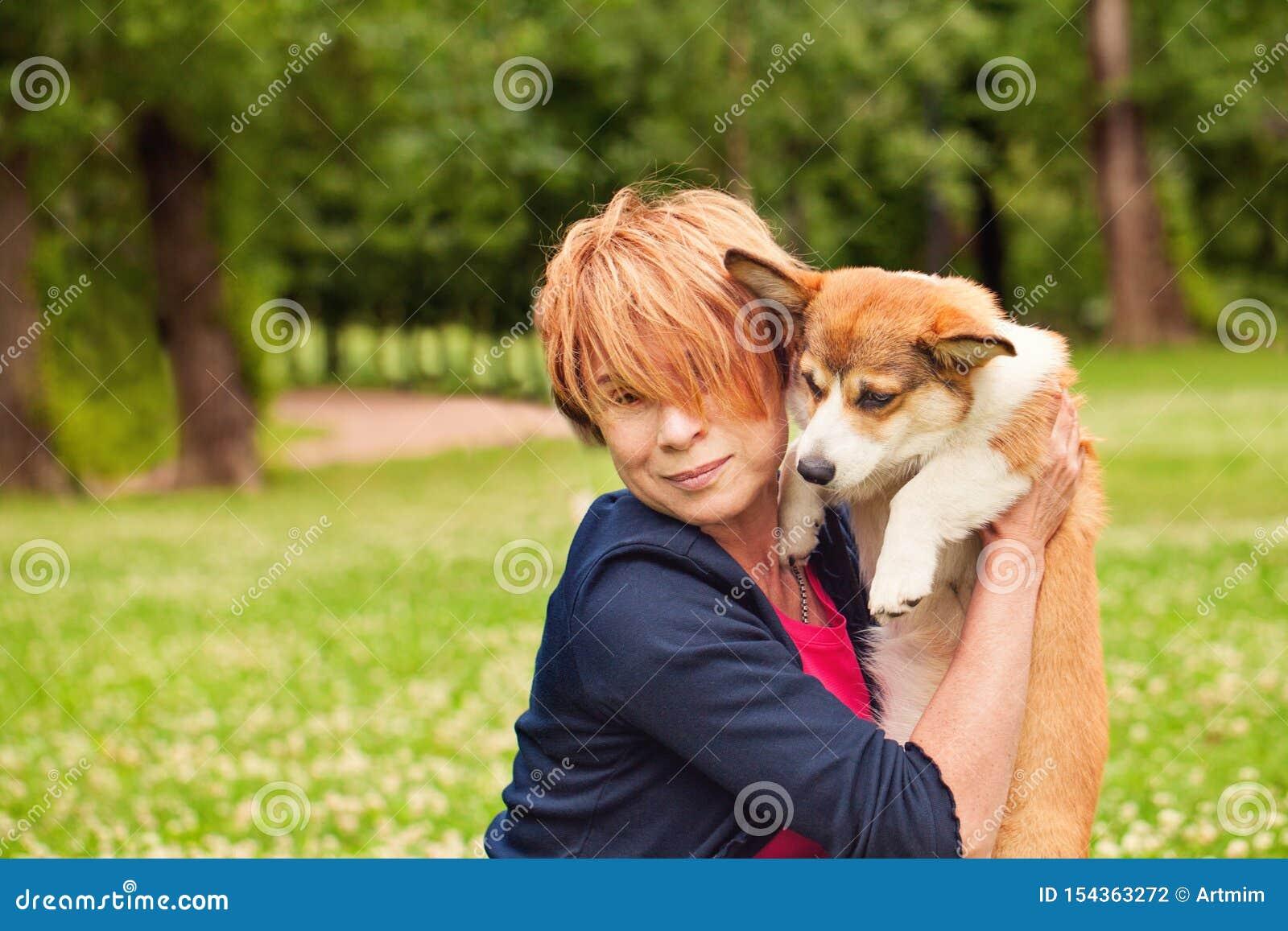 Ευτυχής ώριμη γυναίκα με το κατοικίδιο ζώο σκυλιών κουταβιών στο θερινό πάρκο