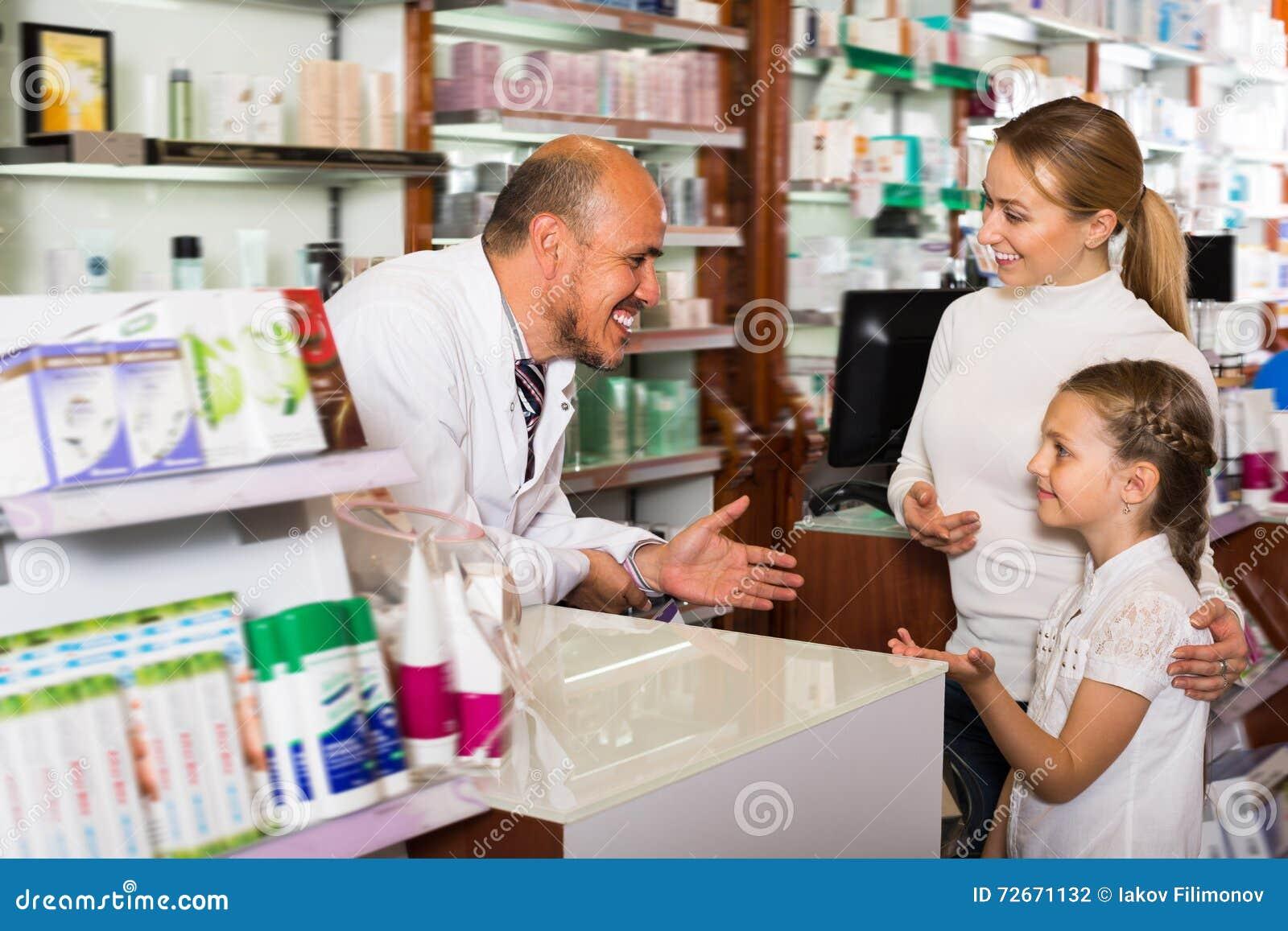 Ευτυχής ώριμος αρσενικός φαρμακοποιός που βοηθά τους πελάτες