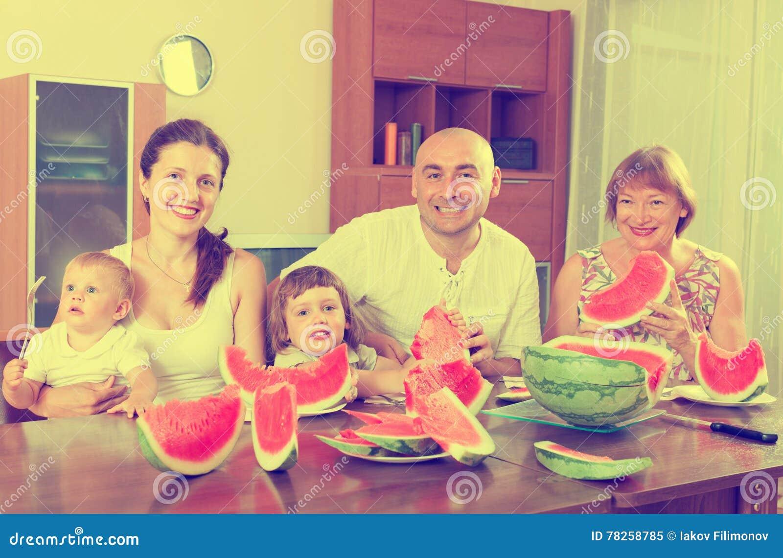 Ευτυχής multigeneration οικογένεια που τρώει το καρπούζι