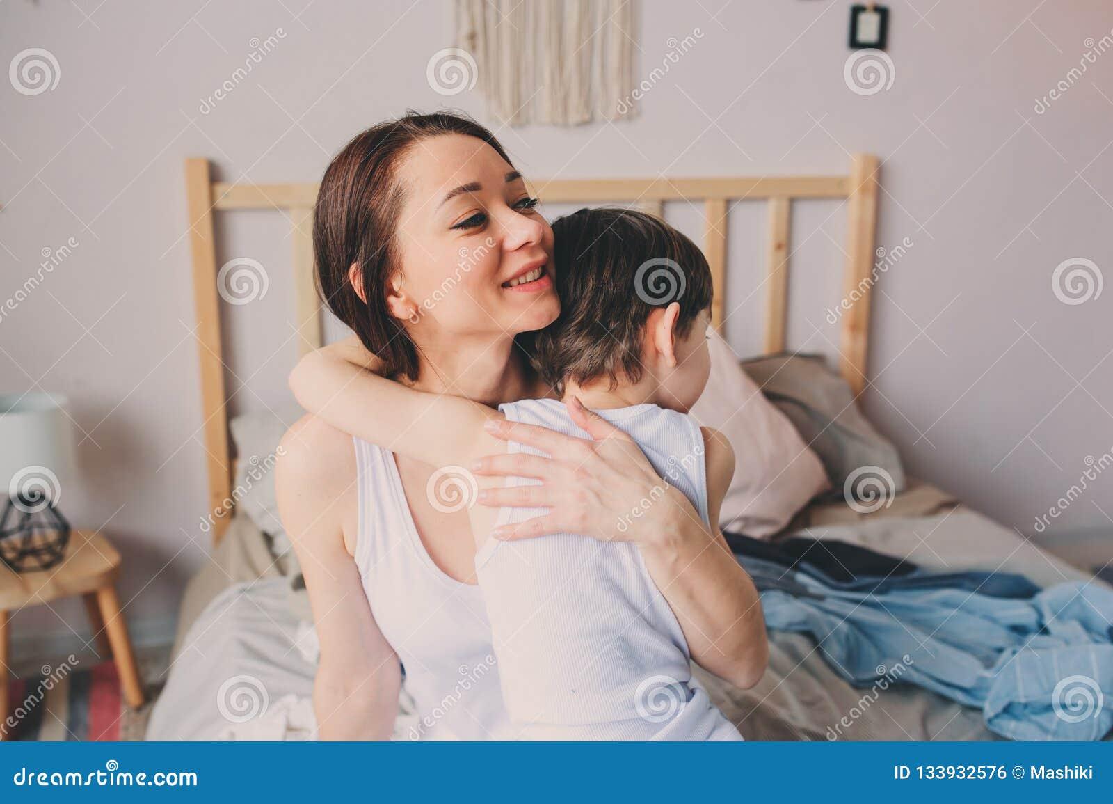 Ευτυχή αγκαλιάσματα μητέρων αγάπης με το γιο παιδιών το πρωί στο κρεβάτι