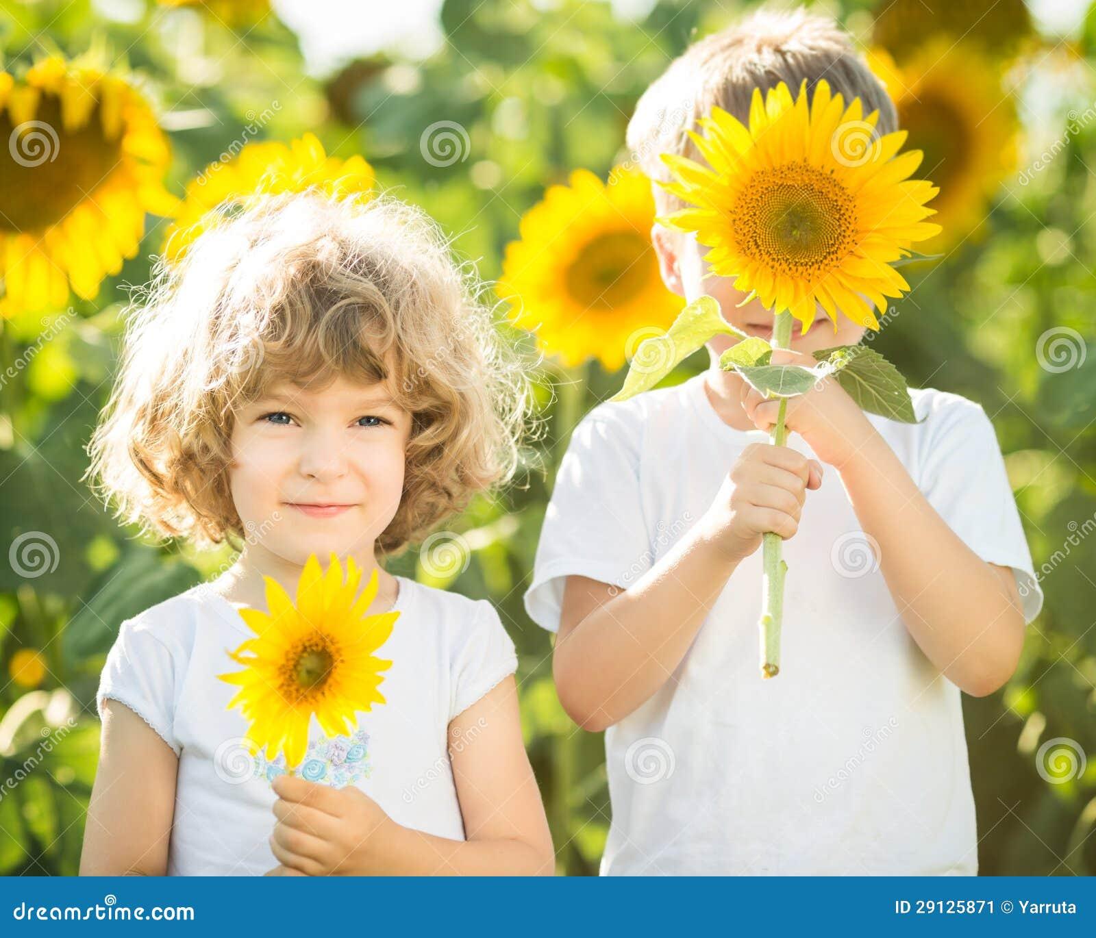 Ευτυχή παιδιά που παίζουν με τους ηλίανθους