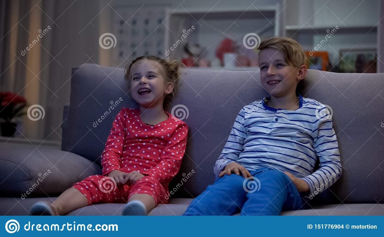 Ευτυχή παιδιά που προσέχουν τον καναπέ συνεδρίασης ταινιών κωμωδίας, που έχει τη διασκέδαση, που γελά από κοινού