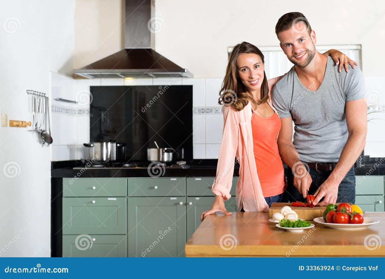 Ευτυχή τέμνοντα λαχανικά ζεύγους στο μετρητή κουζινών